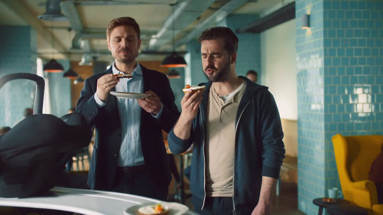 Two men stand in a blue restaurant — one is eating a cream cheese bagel, with a baby carrier on a conveyor belt. It is part of a Philadelphia cream cheese advert banned under gender stereotyping regulations