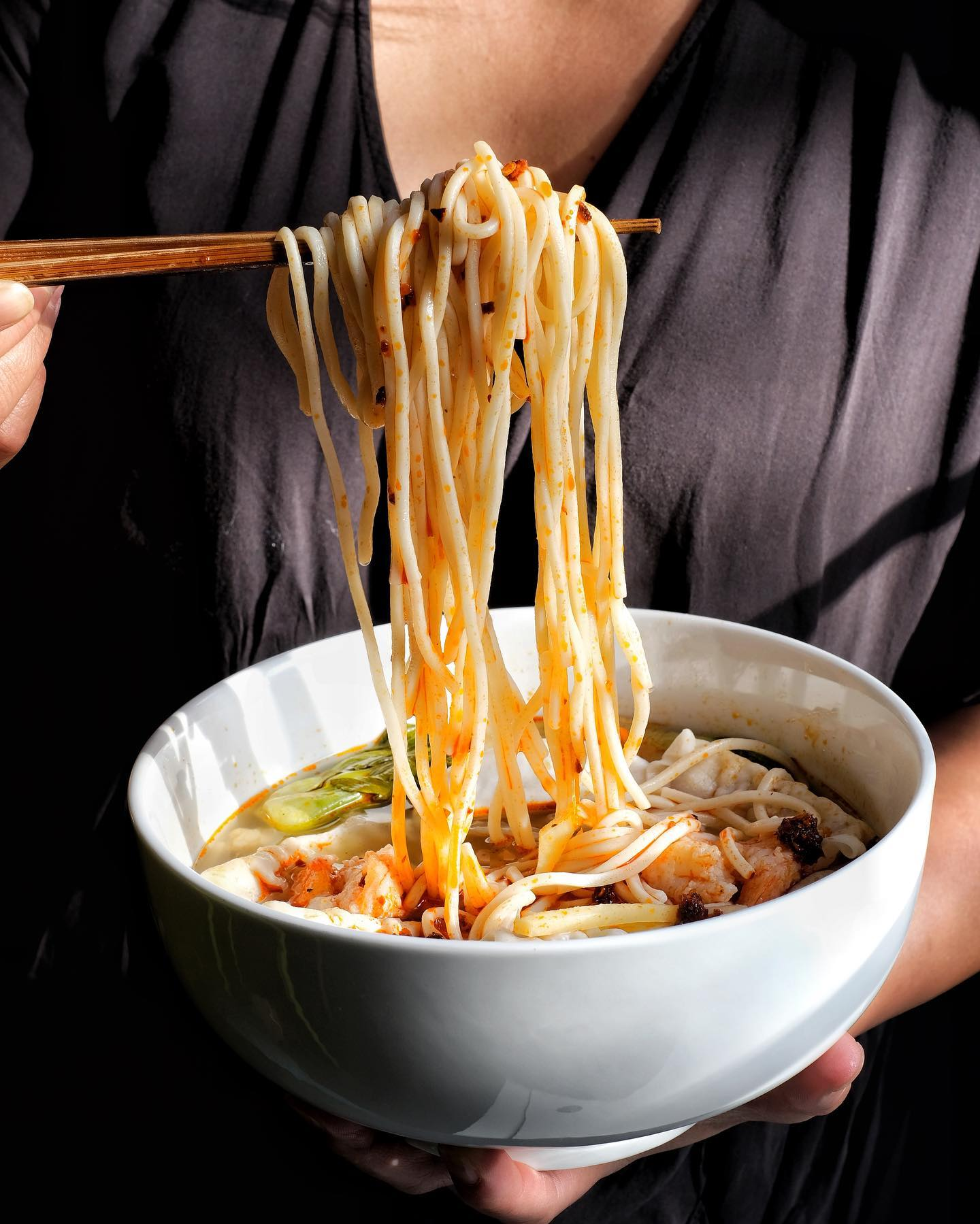 A person lifting noodles from a full bowl using chopsticks