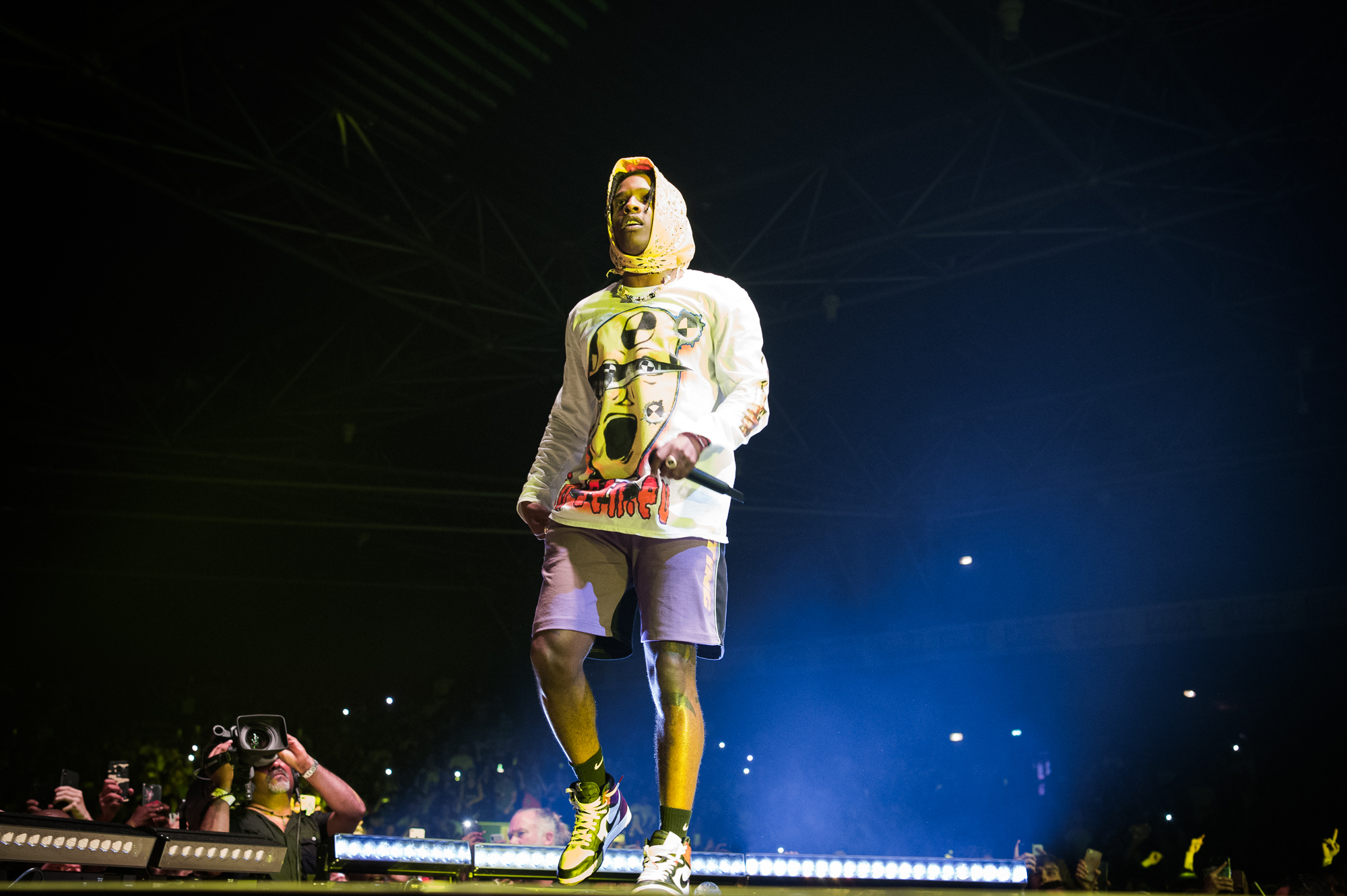 Performer A$AP Rocky onstage, holding a microphone and walking away from the crowd.