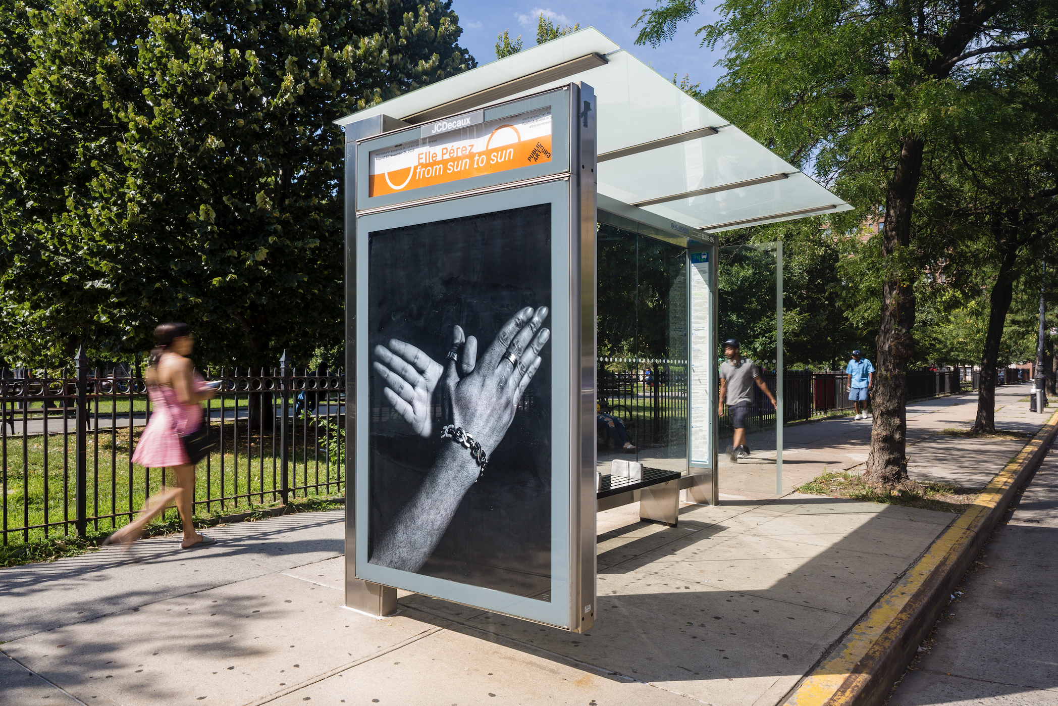 A bus shelter in the Bronx featuring an image of two hands shaking.