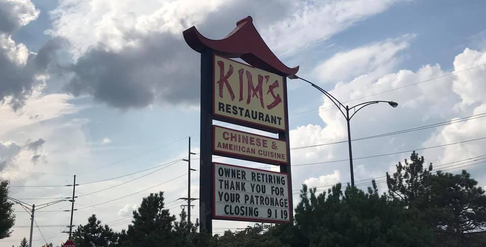 """A red and black pagoda-style roadside sign for Kim's Restaurant reads """"Chinese & American Cuisine"""" with a message that says """"Owner retiring. Thank you for your patronage. Closing 9/1/19"""""""