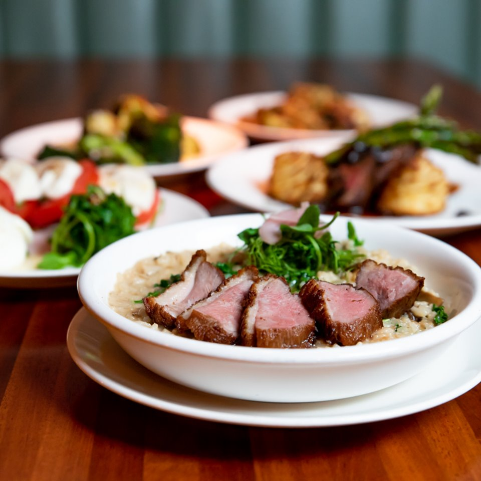 Steak on risotto, caprese salad, and other dishes on plates at the Rotten Bunch restaurant
