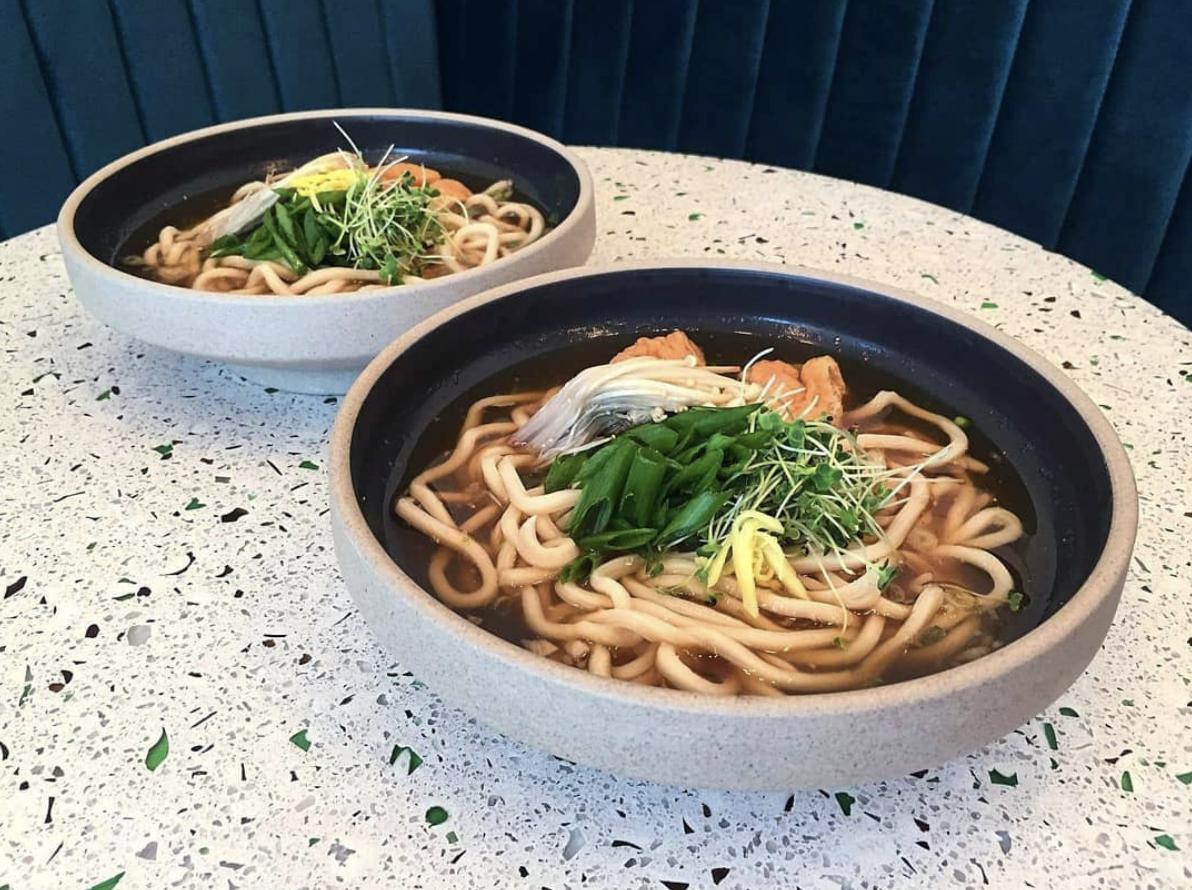 Two bowls of vegan ramen on a white tabletop.