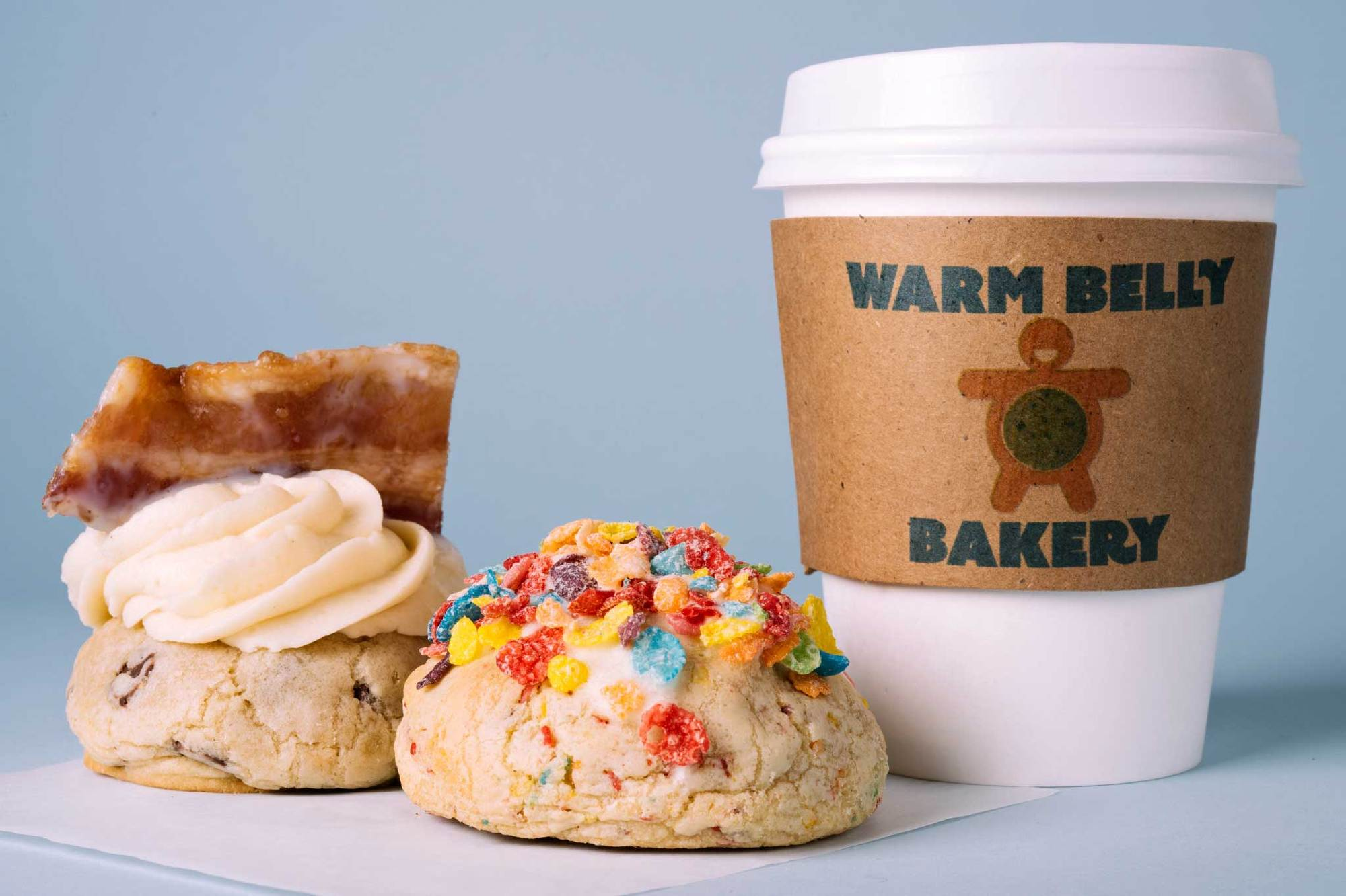 Two cookies and a coffee cup from Warm Belly with lots of colorful toppings.