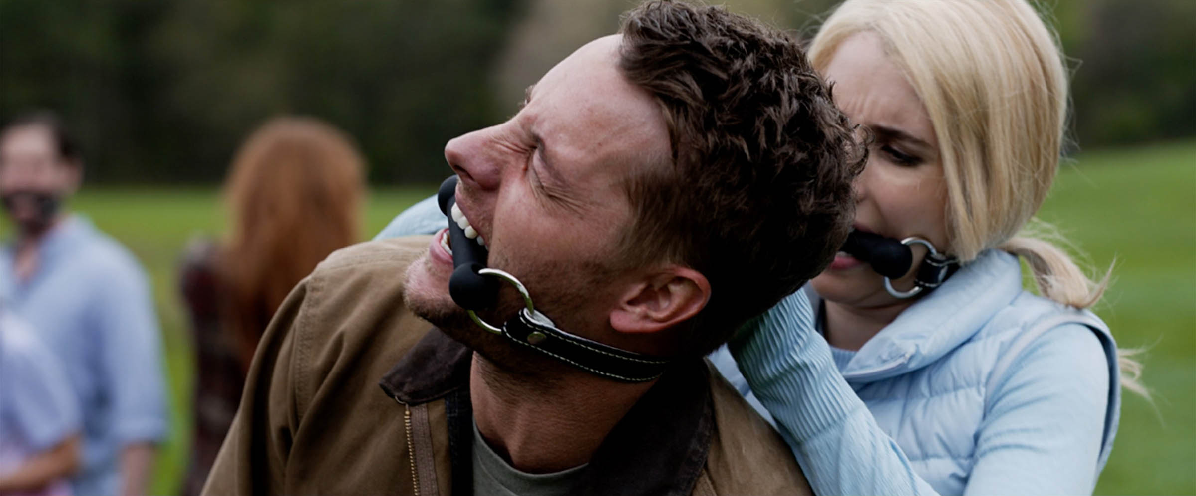 A man wearing a gag appears to be in pain while a woman wearing a similar gag stands close behind him.