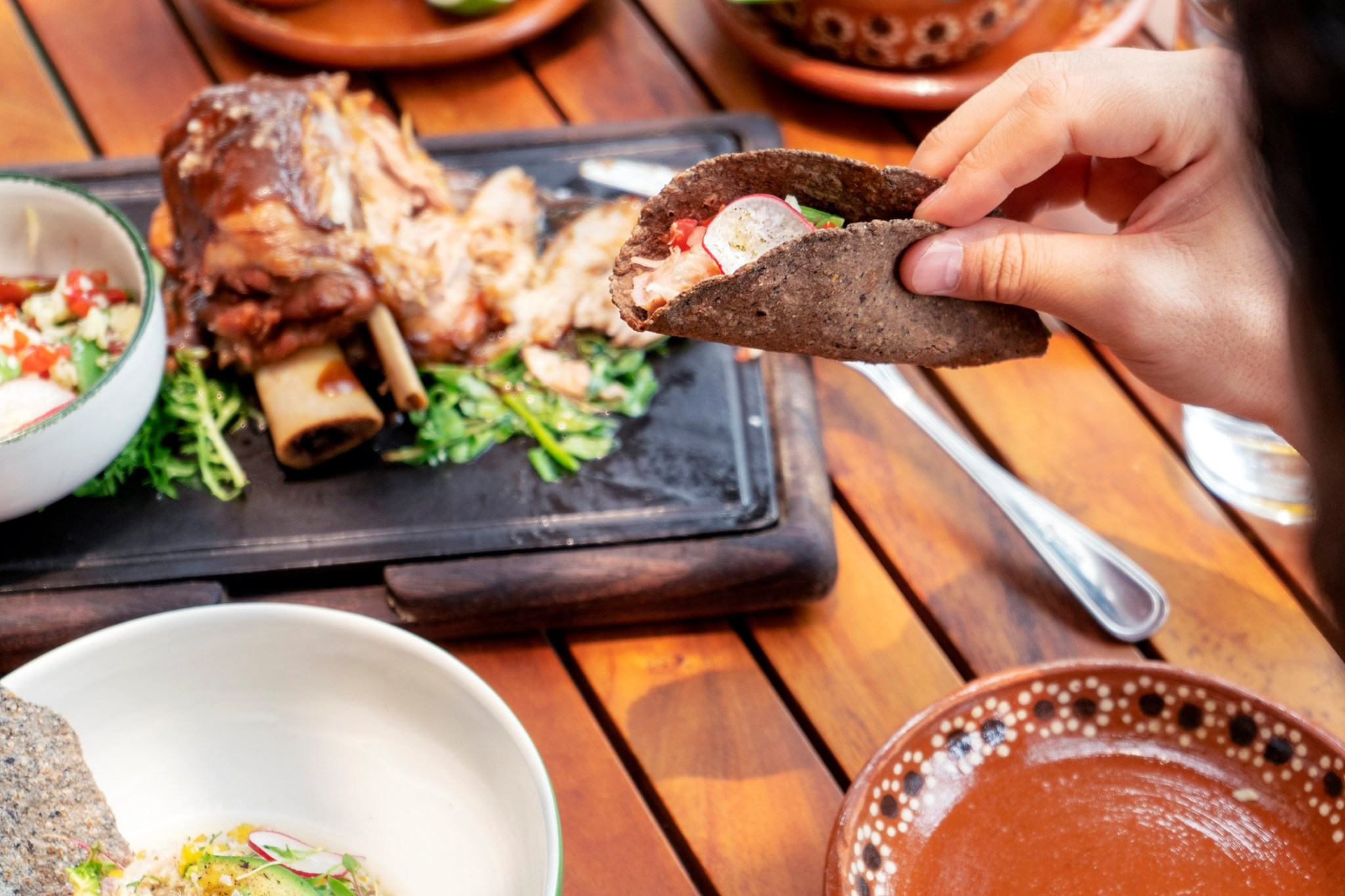 A hand holding a corn tortilla taco with meat on a bone in the background of the table.