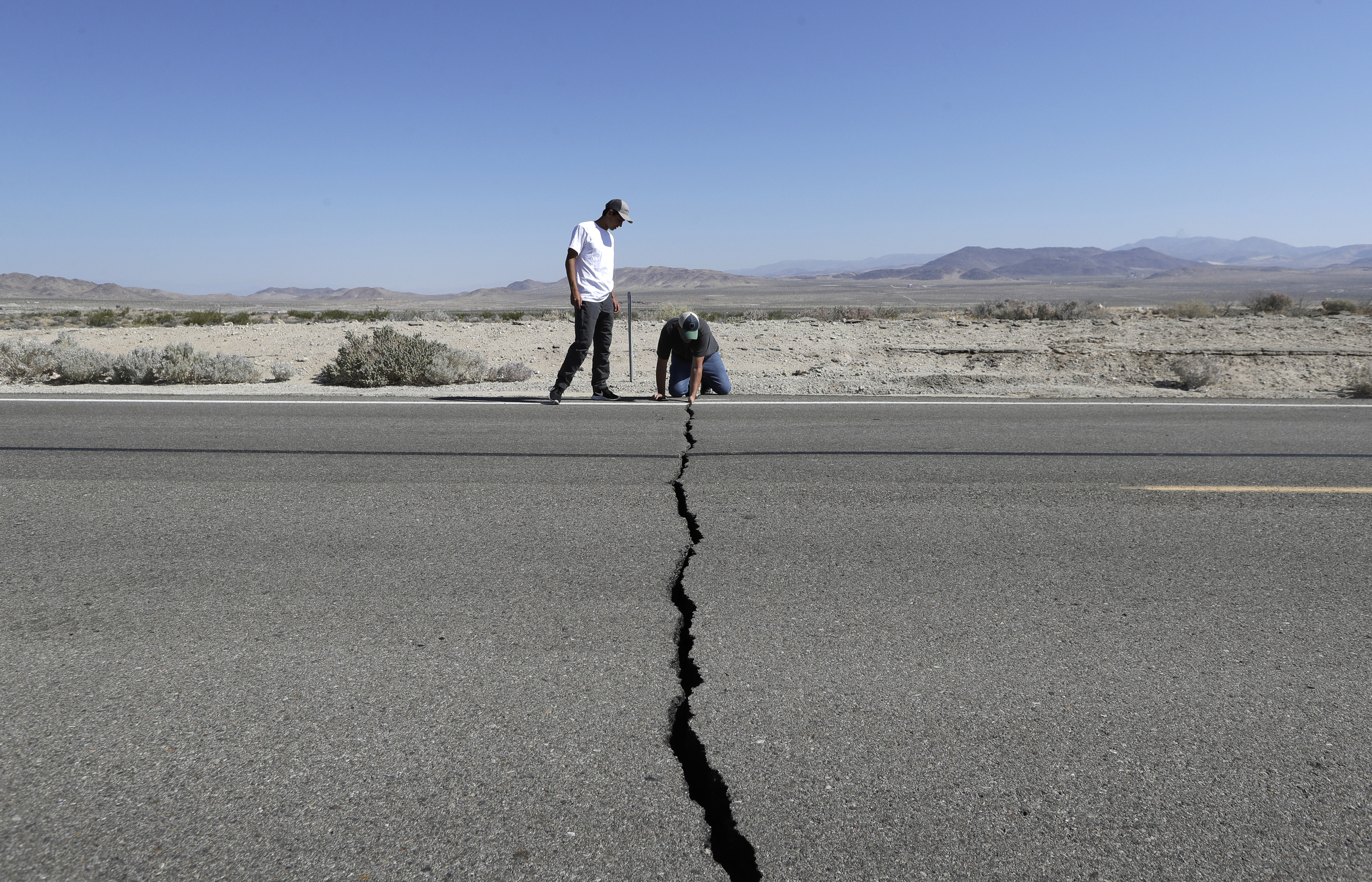 A photo of two men outside, looking at a large, wide crack in the pavement of a road.