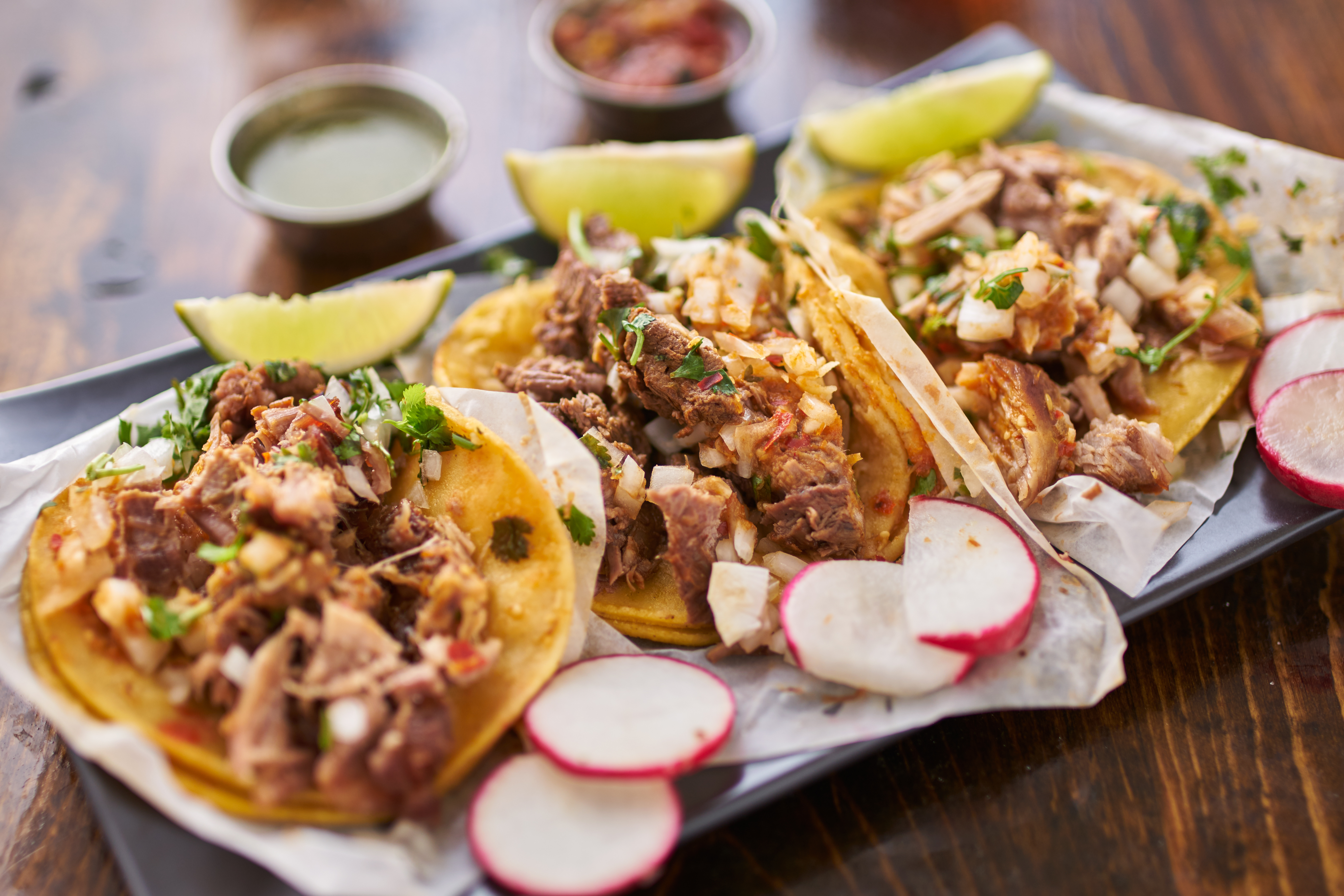 Three tacos in yellow corn tortillas with meat and garnishes.