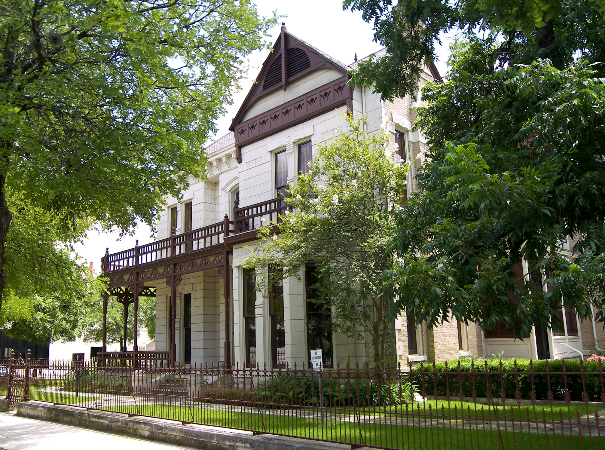 Large, two-story Victorian style building with large porch and verandas and ornate iron railings, white brick or limestone.
