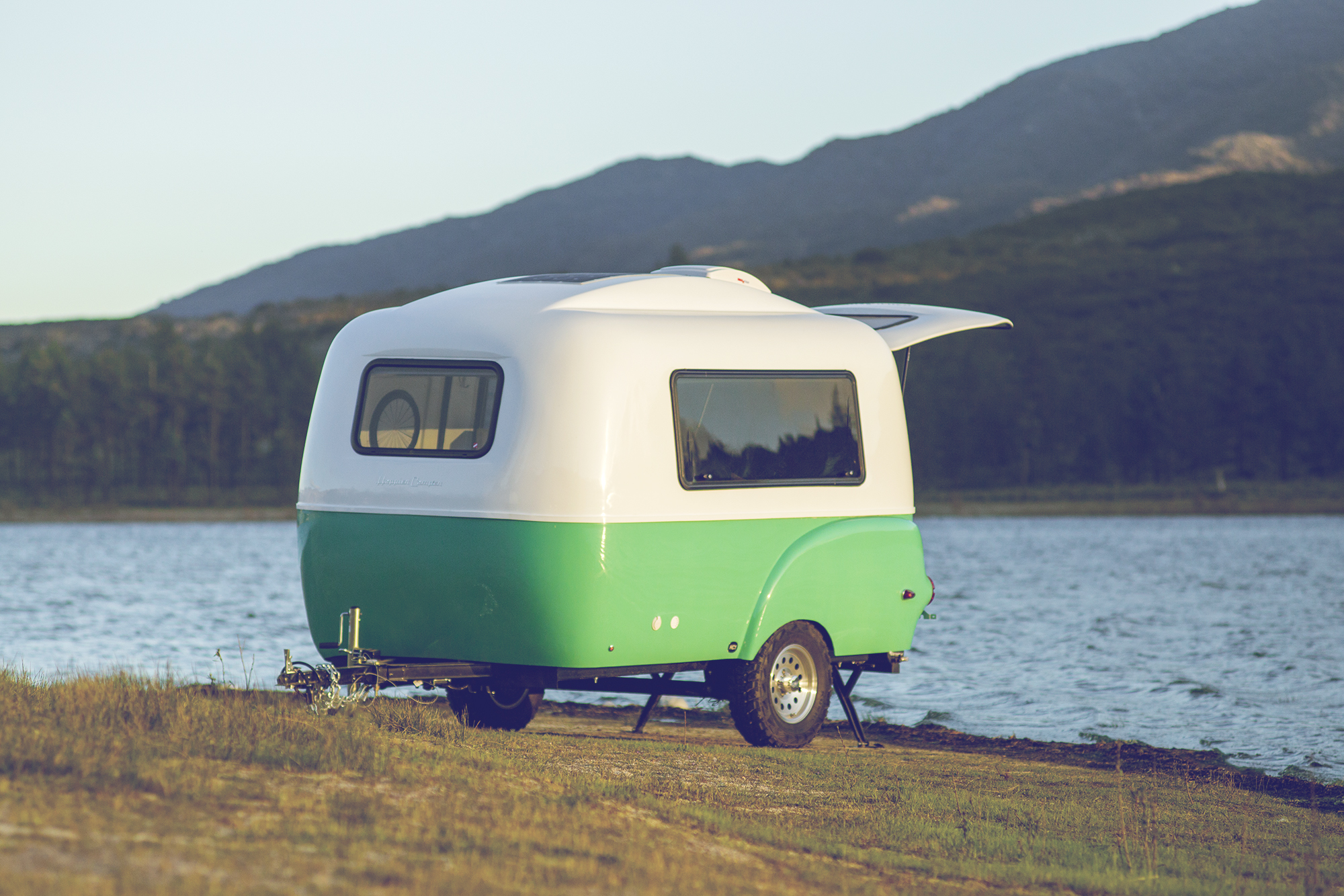 A vintage-styled fiberglass camping trailer in white and green sits in front of a lake.