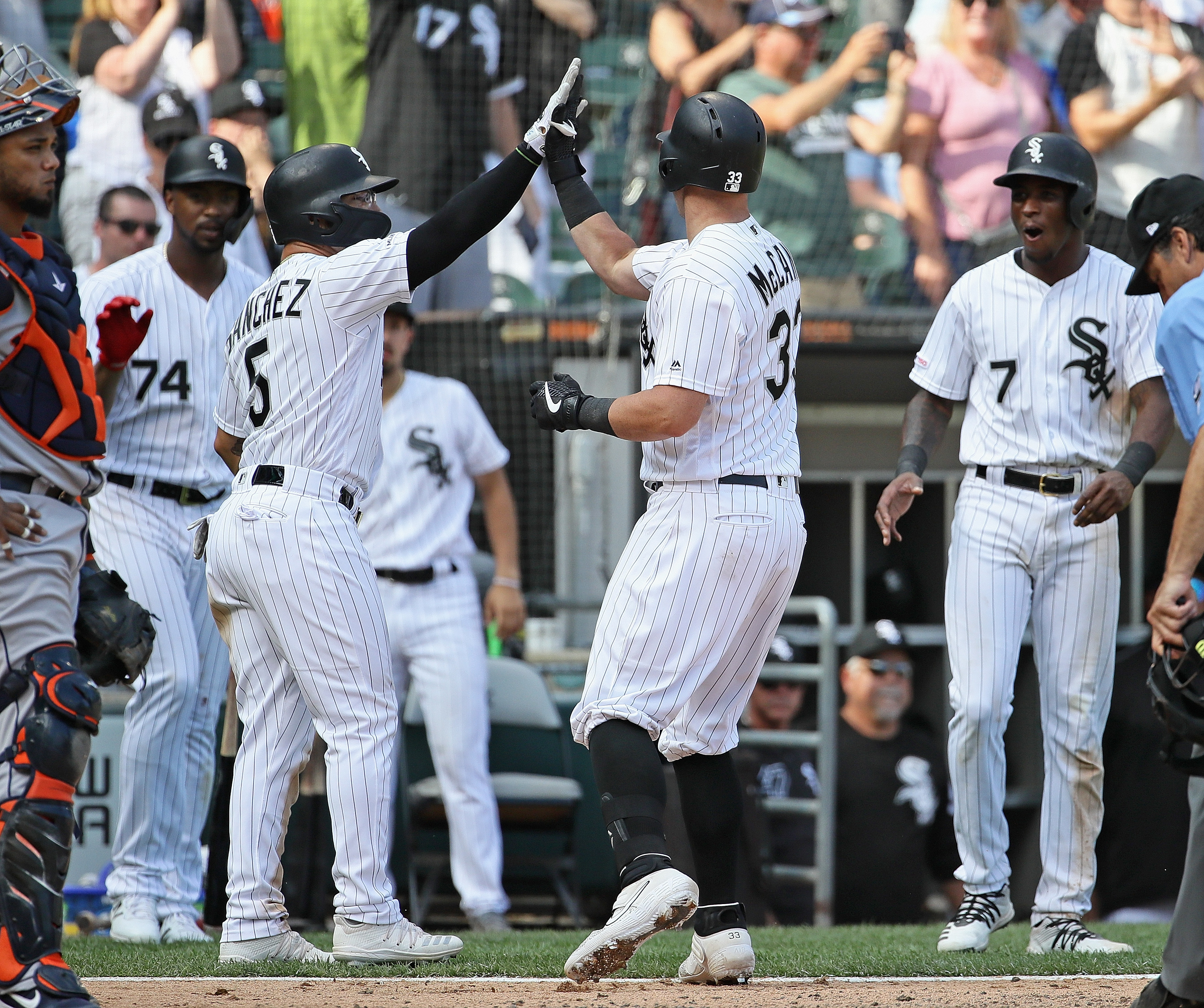 James McCann #33 of the Chicago White Sox celebrates with teammates including Yolmer Sanchez #5 after hitting the game winning, grand slam home run in the 8th inning against the Houston Astros at Guaranteed Rate Field on August 14, 2019 in Chicago, Illino