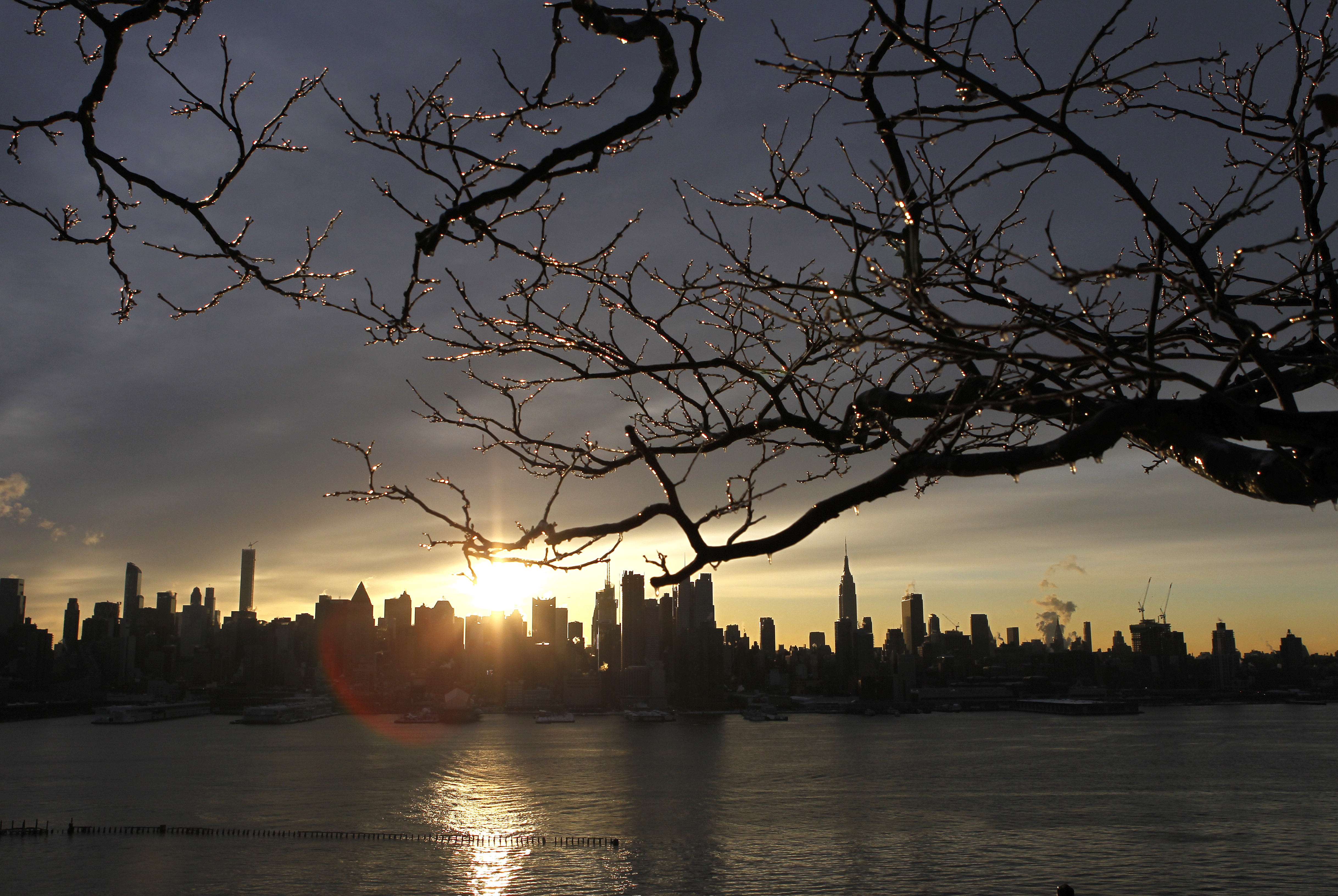 The sun rises behind the skyline of Manhattan in New York