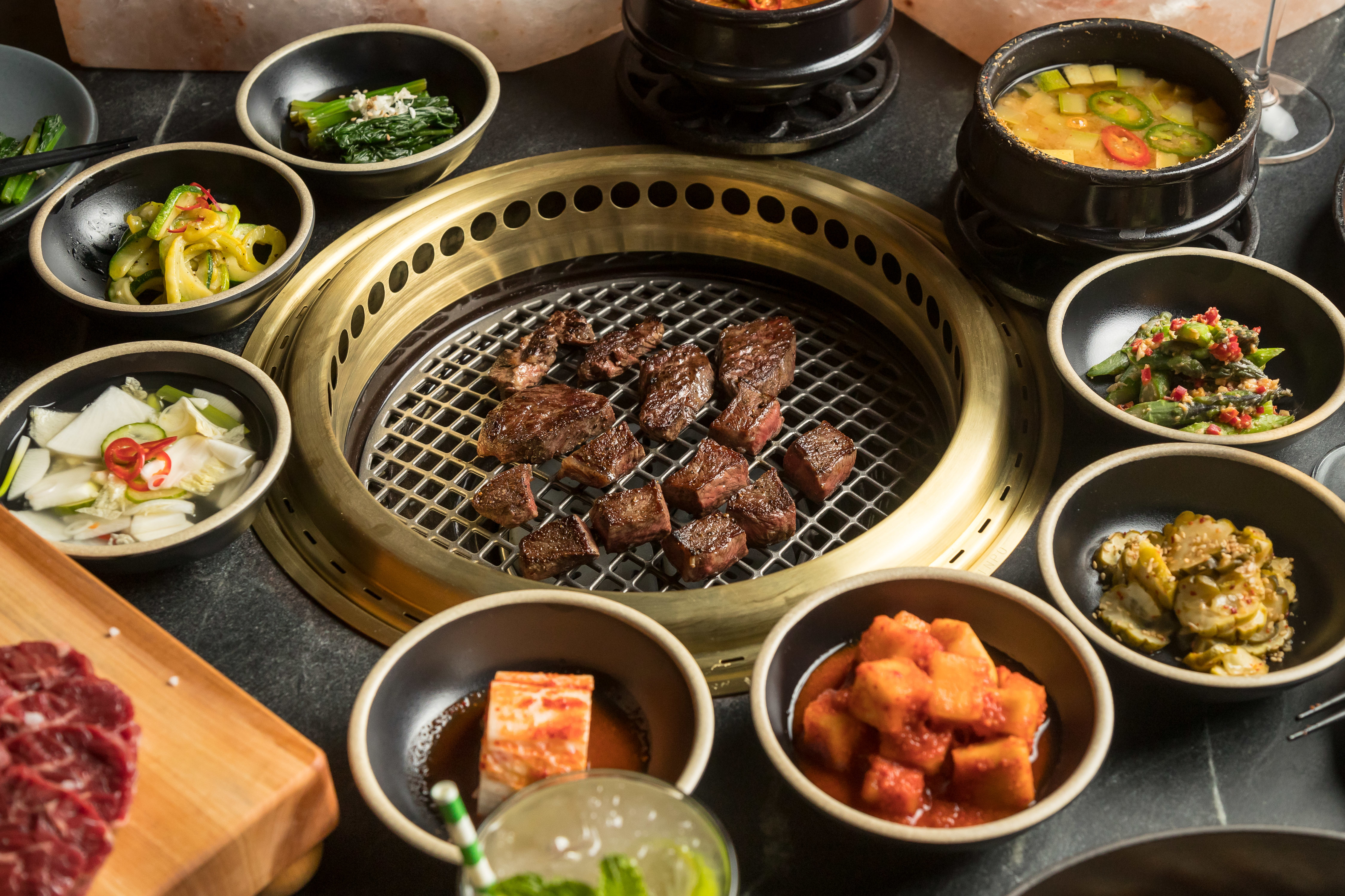 Meat on grill surrounded by bowls filled with vegetables and toppings