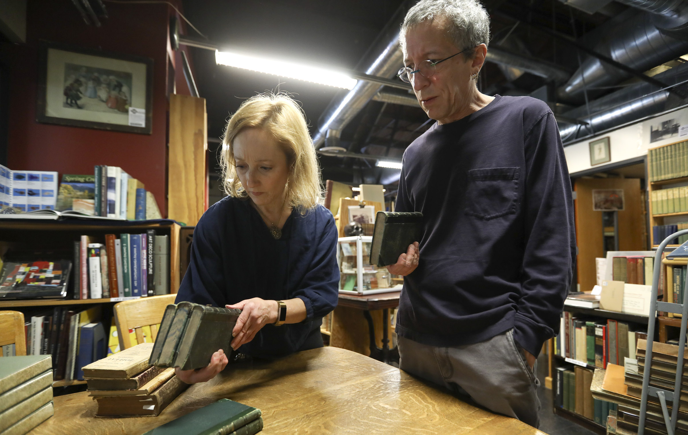 Catherine and Tony Weller, co-owners of Weller Book Works, look through newly acquired books that will be added to the rare book section at the store in Salt Lake City on Friday, Aug. 9, 2019. The book store is celebrating its 90th anniversary.