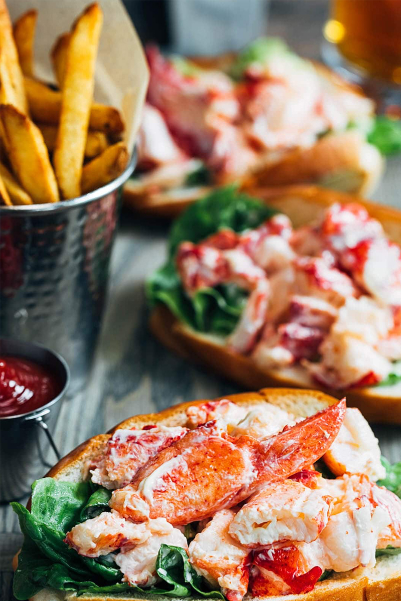 A spread of lobster rolls with a side of fries and ketchup.