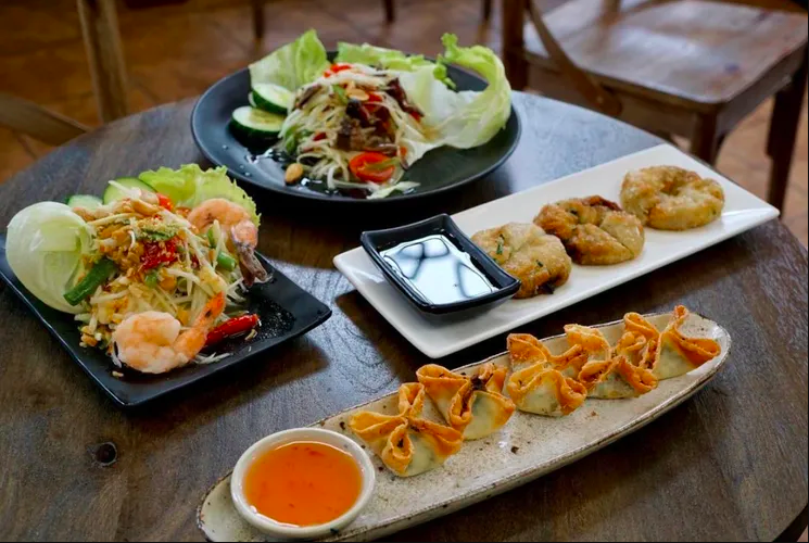 Four dishes sit on a table: in the front, wontons line up on an oblong plate, with a shrimp salad, greens, and fried disc-shaped appetizers on the other plates