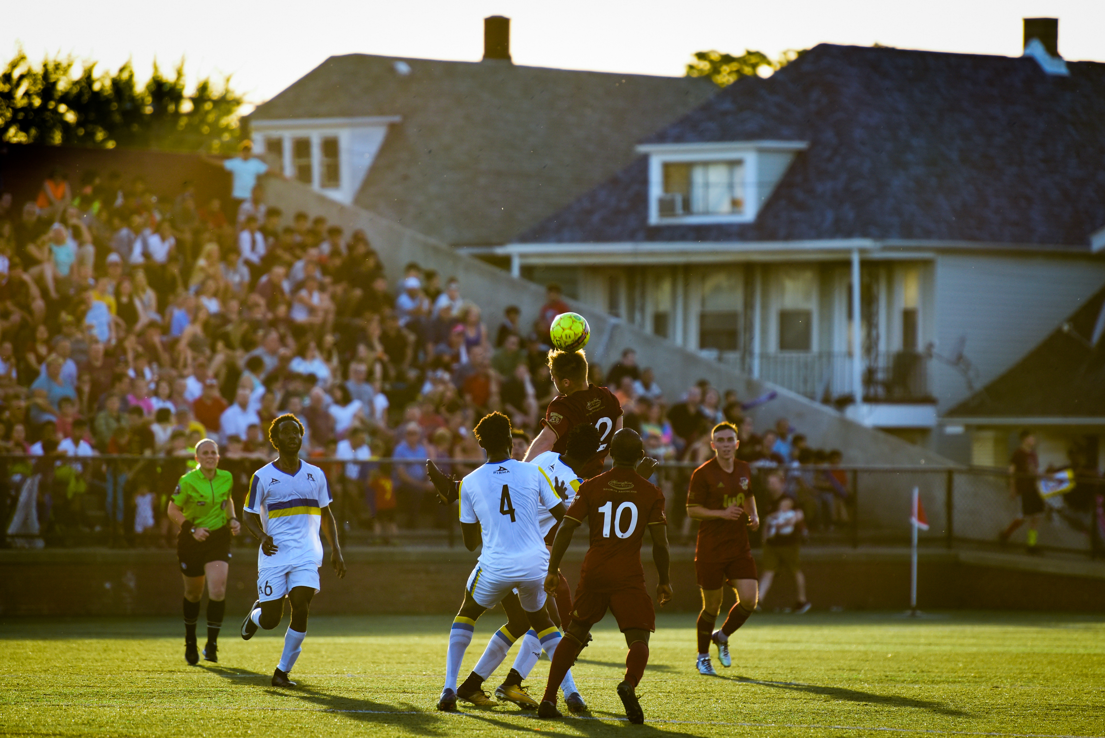 A soccoer player strikes a header in a crowded group