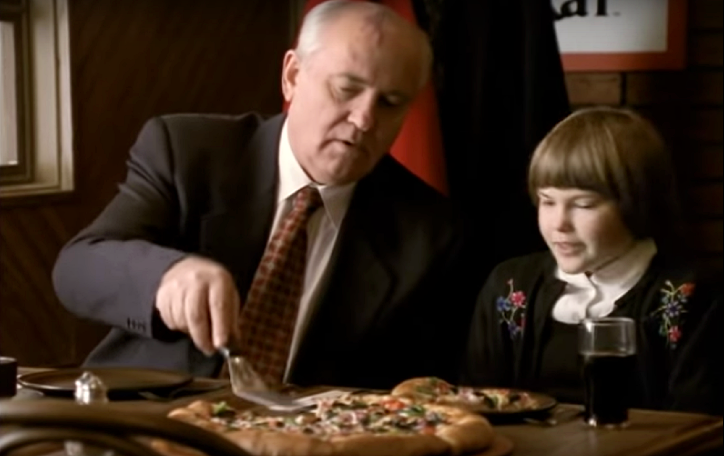 An older man and a 10-year-old girl seated at a table, a pizza in front of them.