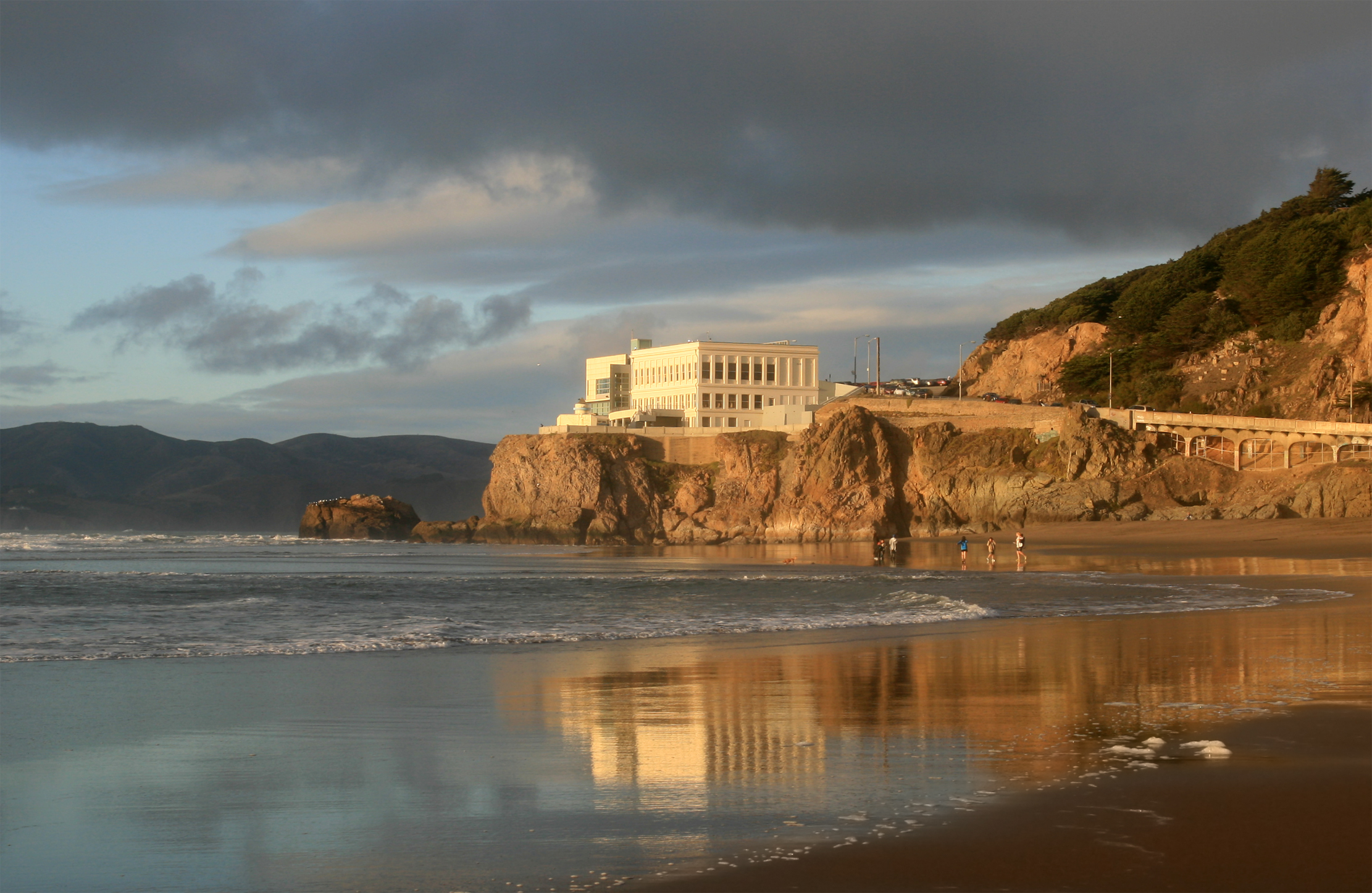 The Cliff House, a white concrete building, atop a cliff ovrerlooking the Pacific Ocean.