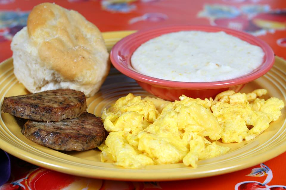 A plate of scrambled eggs, two sausage patties, a biscuit, and bowl of grits