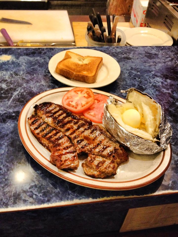 Steak with buttered baked potato and tomatoes in the foreground, toast on a white plate in the background