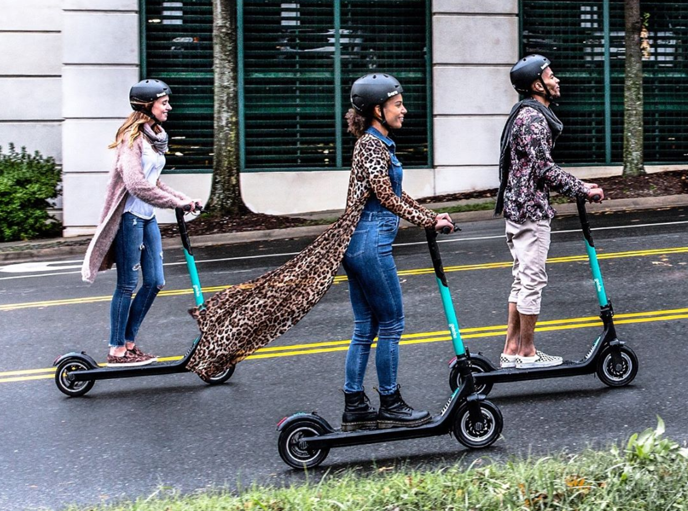 Two women and a man head to the right on turquoise-accented e-scooters.