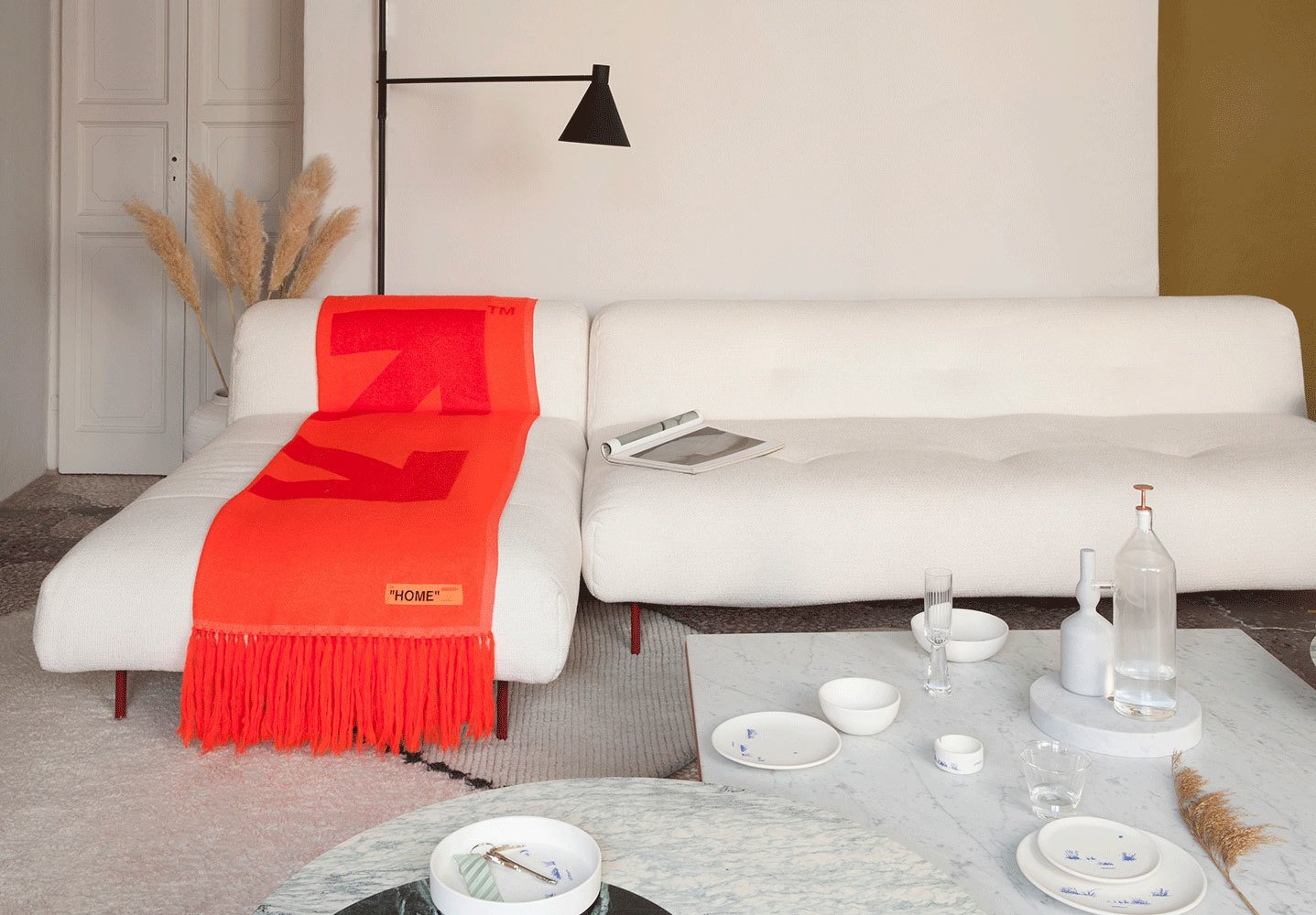 White couch with red throw and a smattering of plates and bowls.