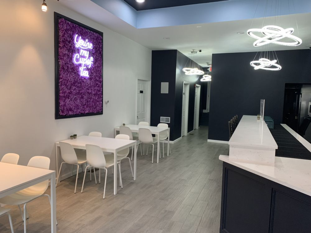 "A black counter with a white top aligns with the right wall, while white tables and chairs line a white wall to the left, which features a frame full of purple flowers and a neon sign reading ""you're my cup of tea"""