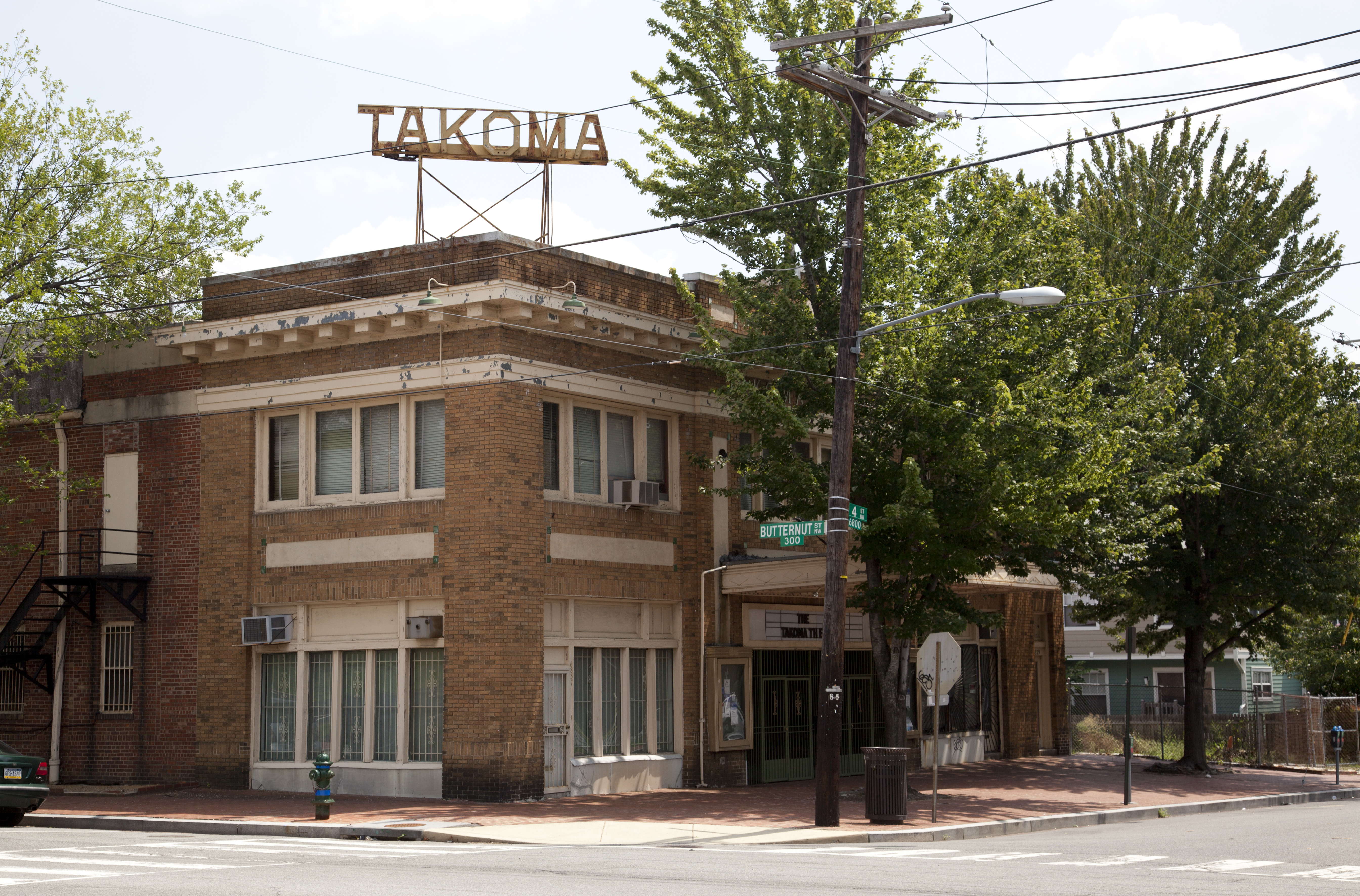 The old Takoma Theatre at the intersection of 4th and Butternut streets NW, a two-story brick building.