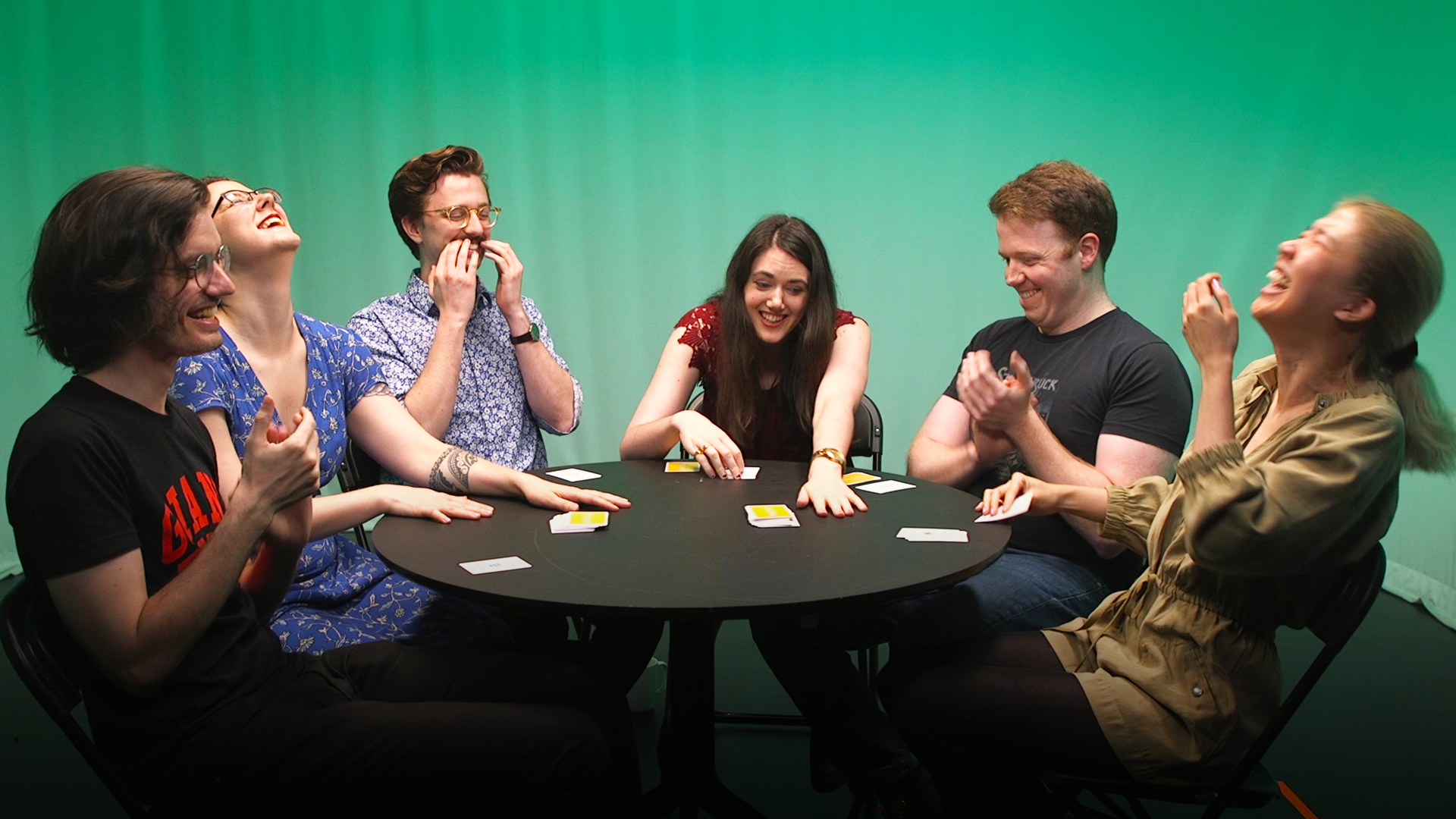 A group of six friends laugh as they sit around a table playing a card game together.