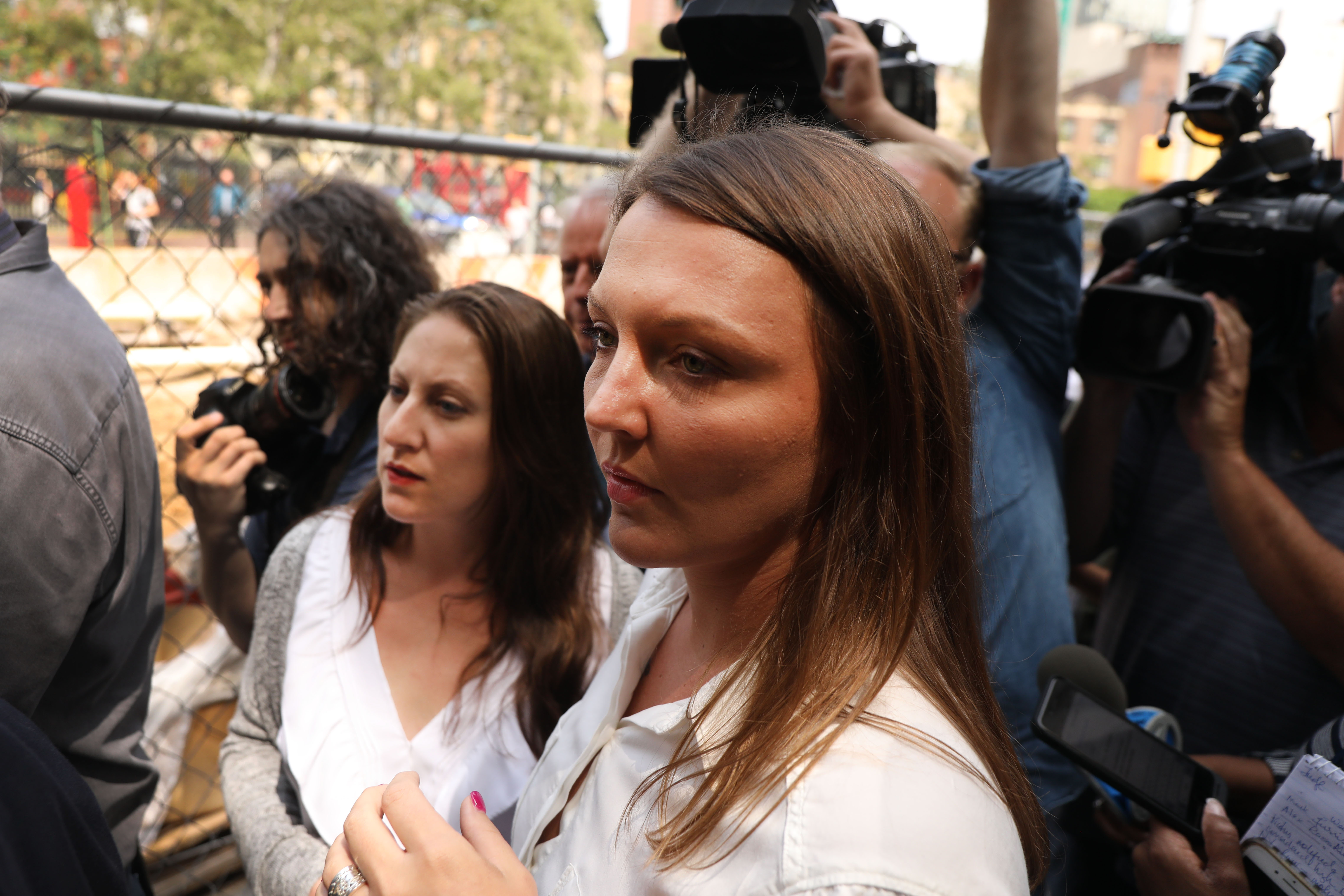 Michelle Licata (left) and Courtney Wild, two women who say Jeffrey Epstein abused them, stand surrounded by cameras and reporters outside a Manhattan courthouse after a hearing on sex trafficking charges against Epstein.