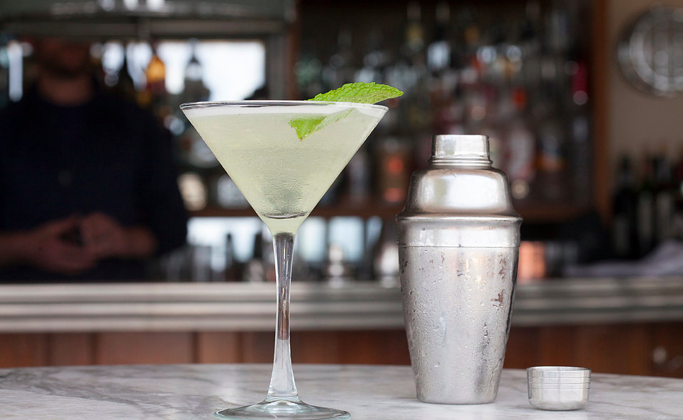 A light green cocktail is served in a martini glass on a marble bar, with a silver cocktail shaker to the right and bar shelves visible in the background