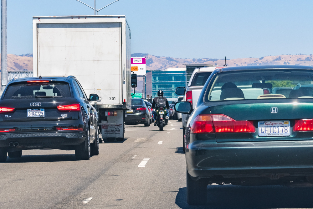 Heavy traffic on one of the freeways crossing Silicon Valley; motorcyclist splitting lanes visible among cars.
