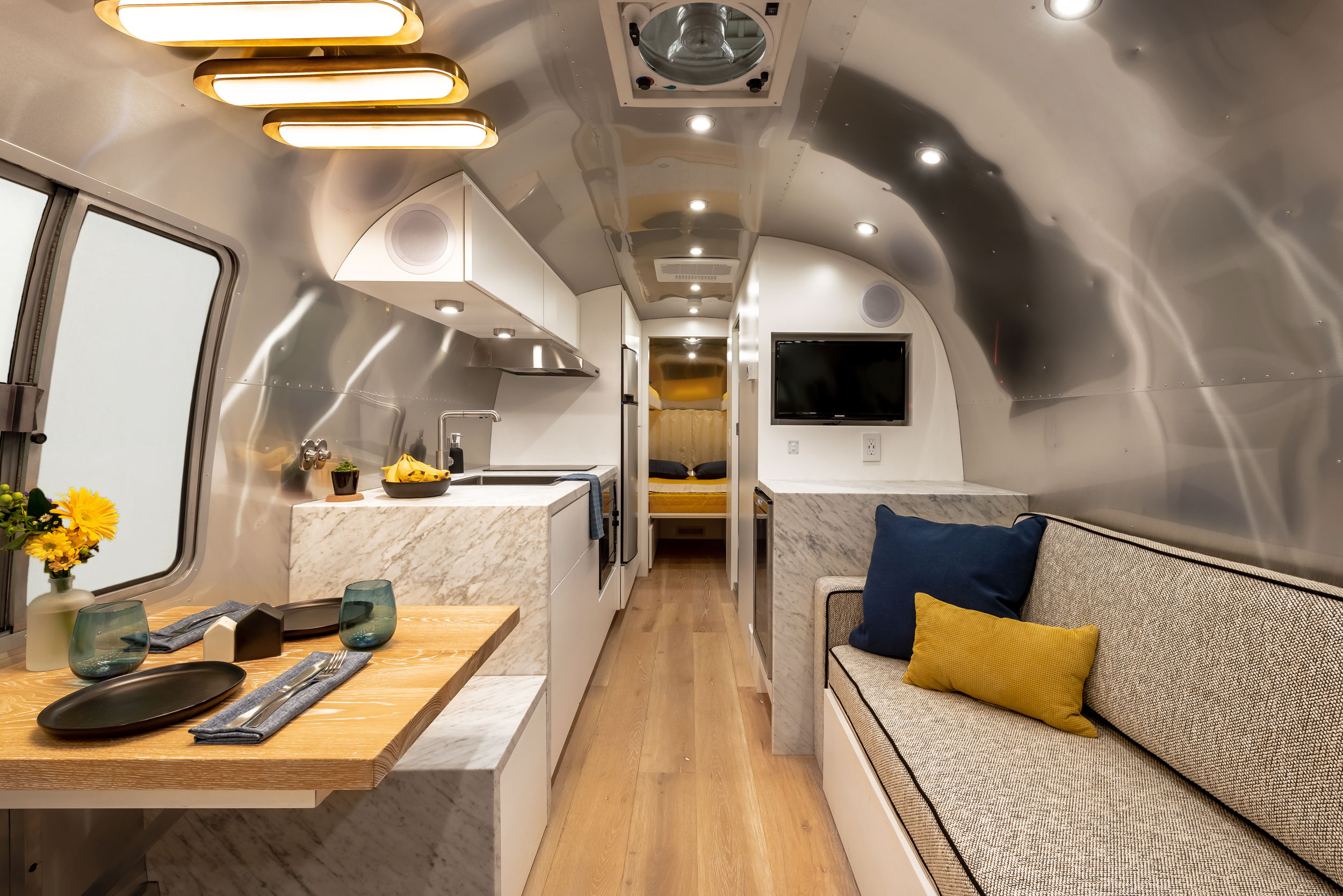 The interior of a shiny aluminum Airstream renovated in blues, whites, and grays.