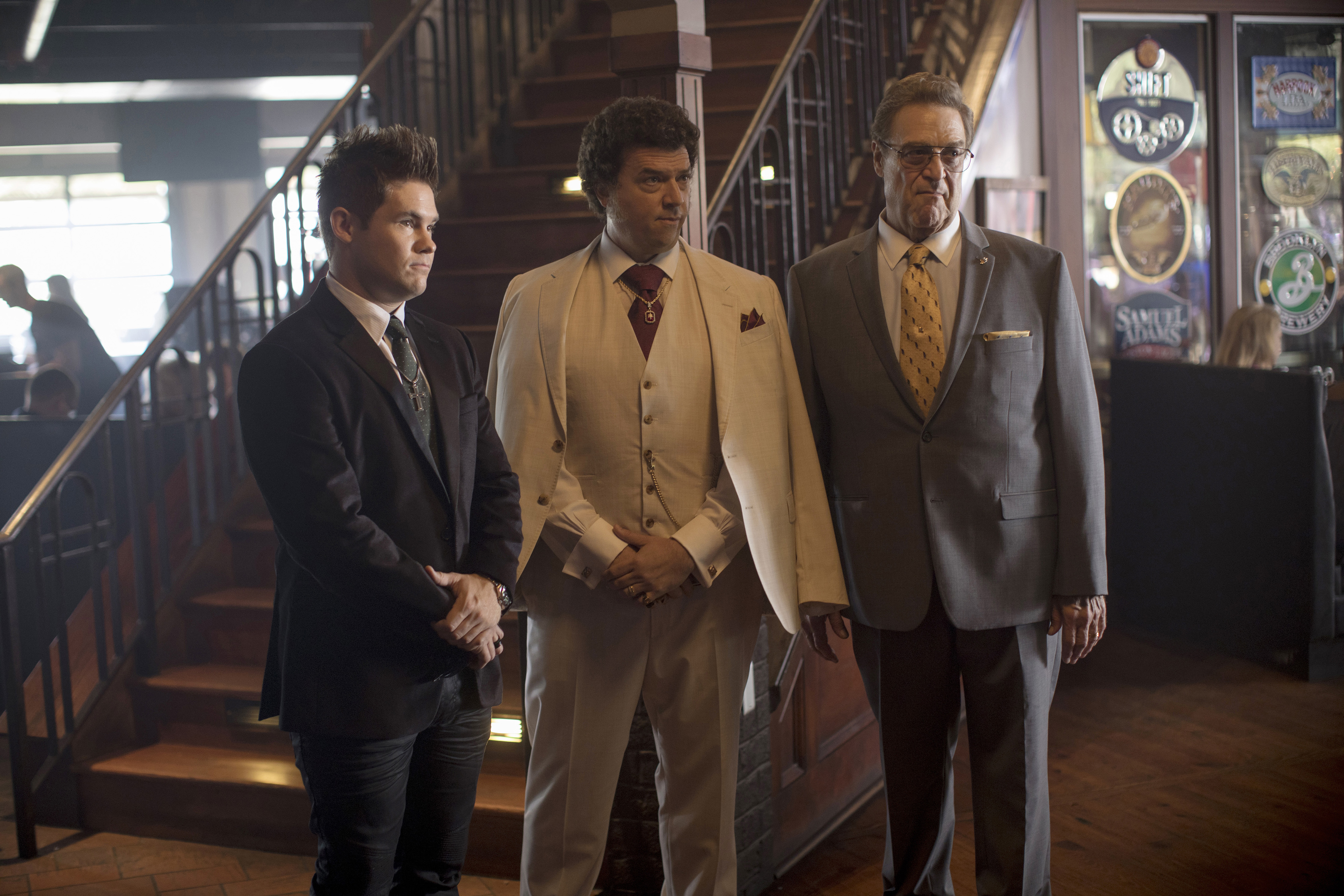 "Three men in the cast of ""The Righteous Gemstones"" wearing suits and standing beside an interior staircase."