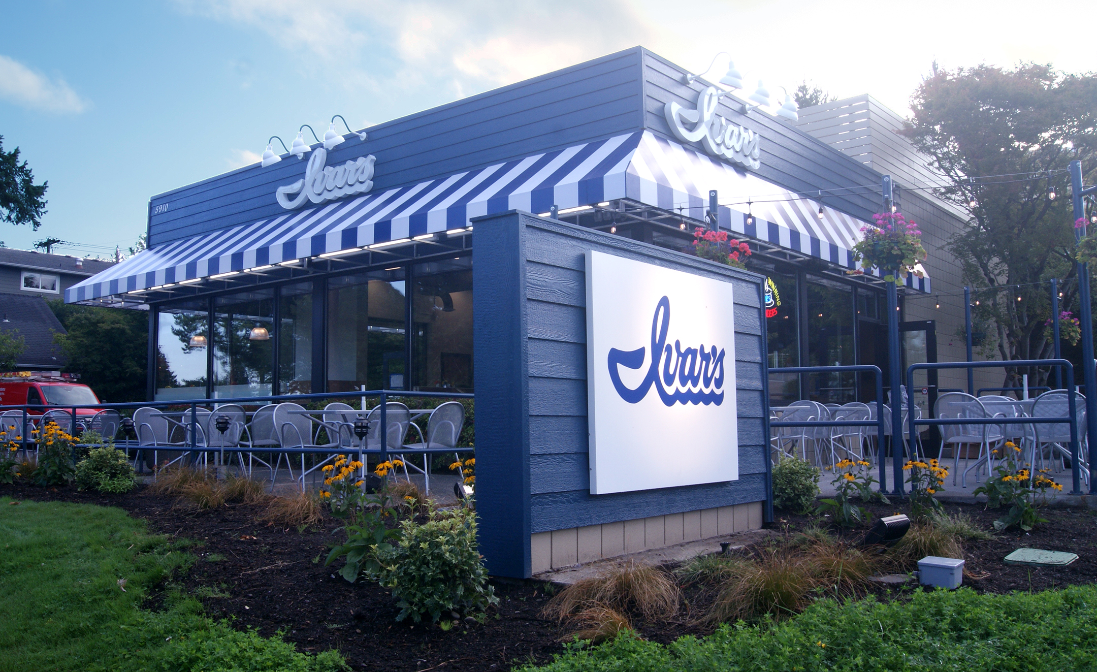 A sunny, exterior view of Ivar's Seafood Bar in Kirkland, with patio seating and the chain's signature white and blue colors.