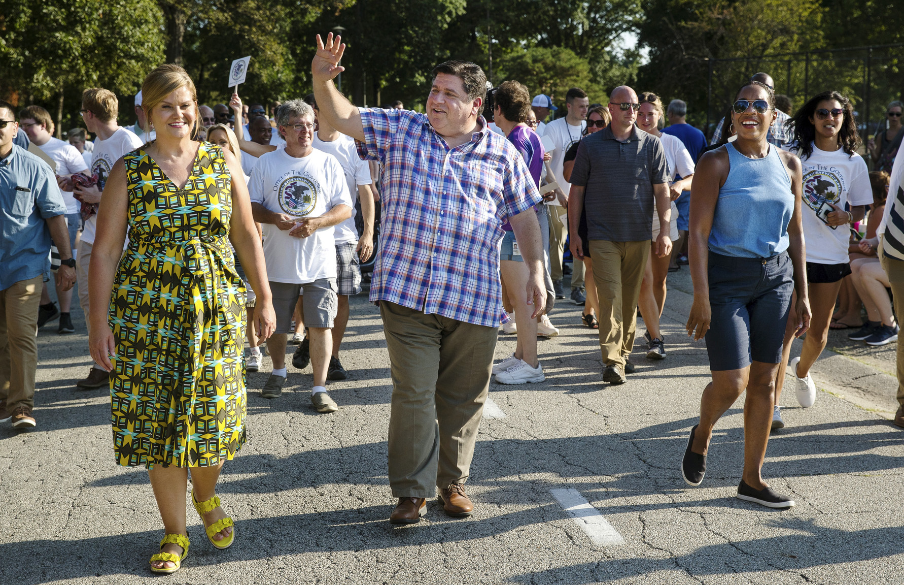Gov. J.B. Pritzker waves while walking in the Illinois State Fair Twilight Parade on Aug. 8, 2019, in Springfield.