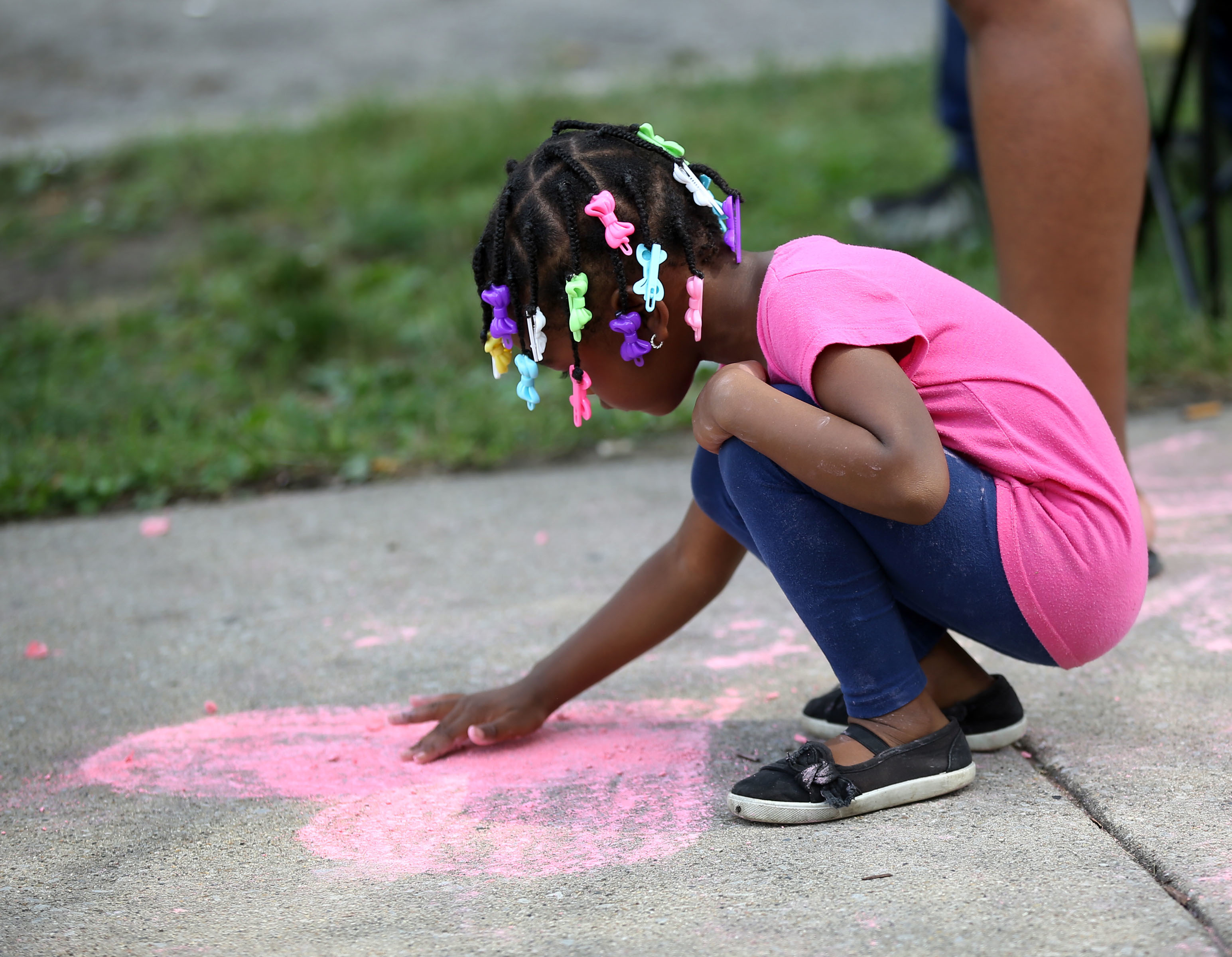 A little girl draws on the sidewalk at a block party in August 2018.
