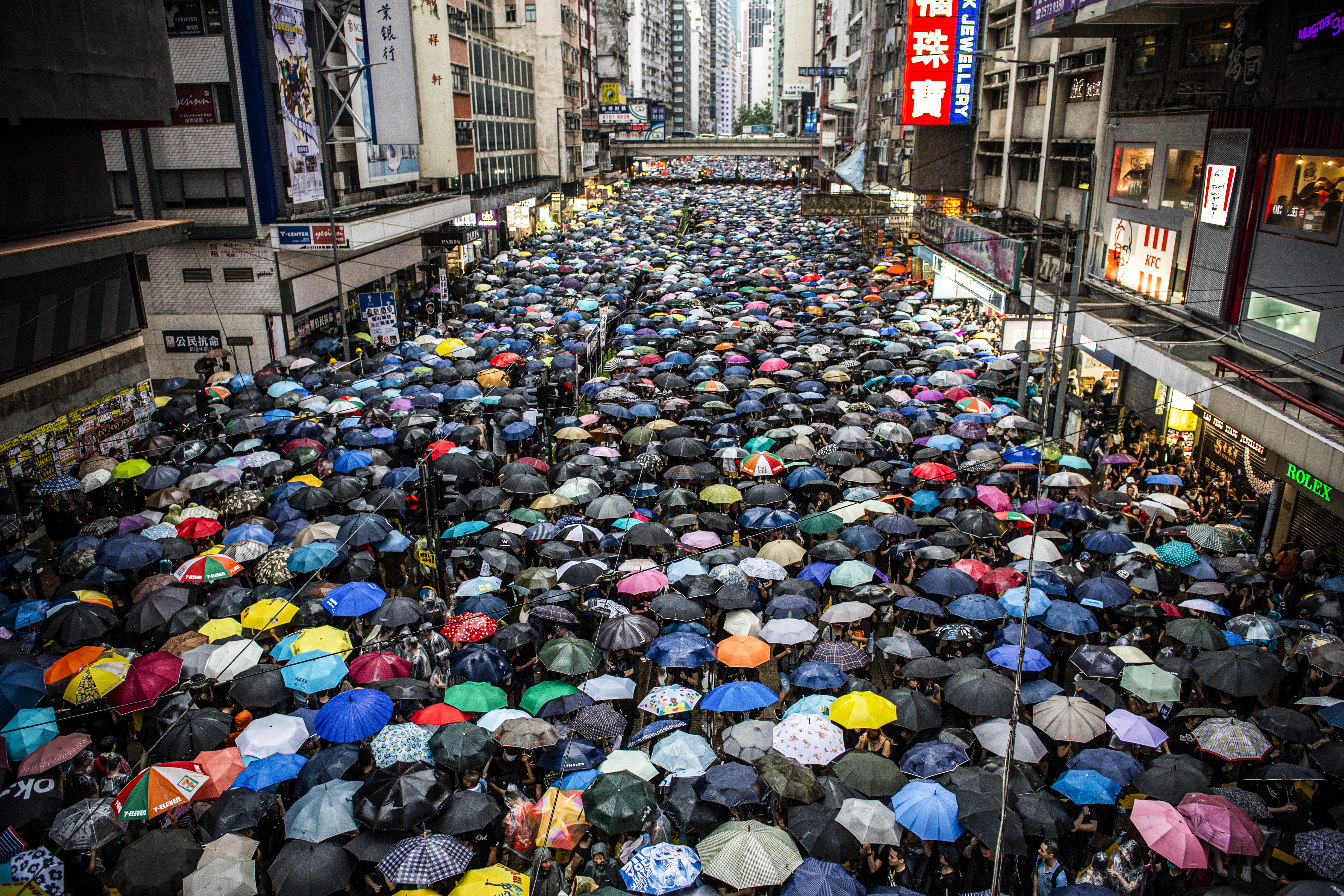 A street in Hong Kong filled with protesters under umbrellas.
