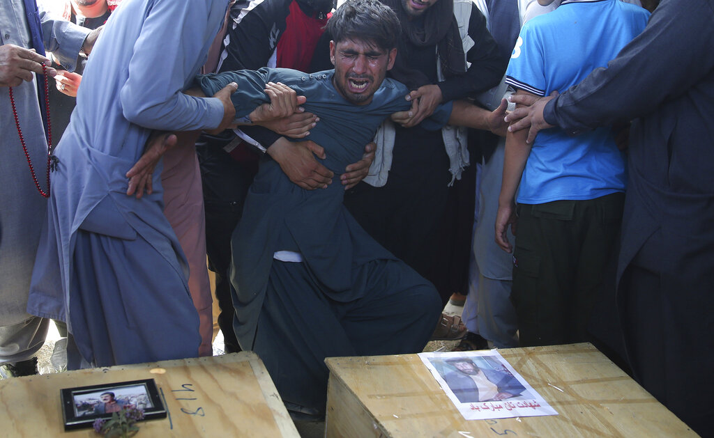 A relative wails near the coffins of victims of the Dubai City wedding hall bombing during a mass funeral in Kabul, Afghanistan