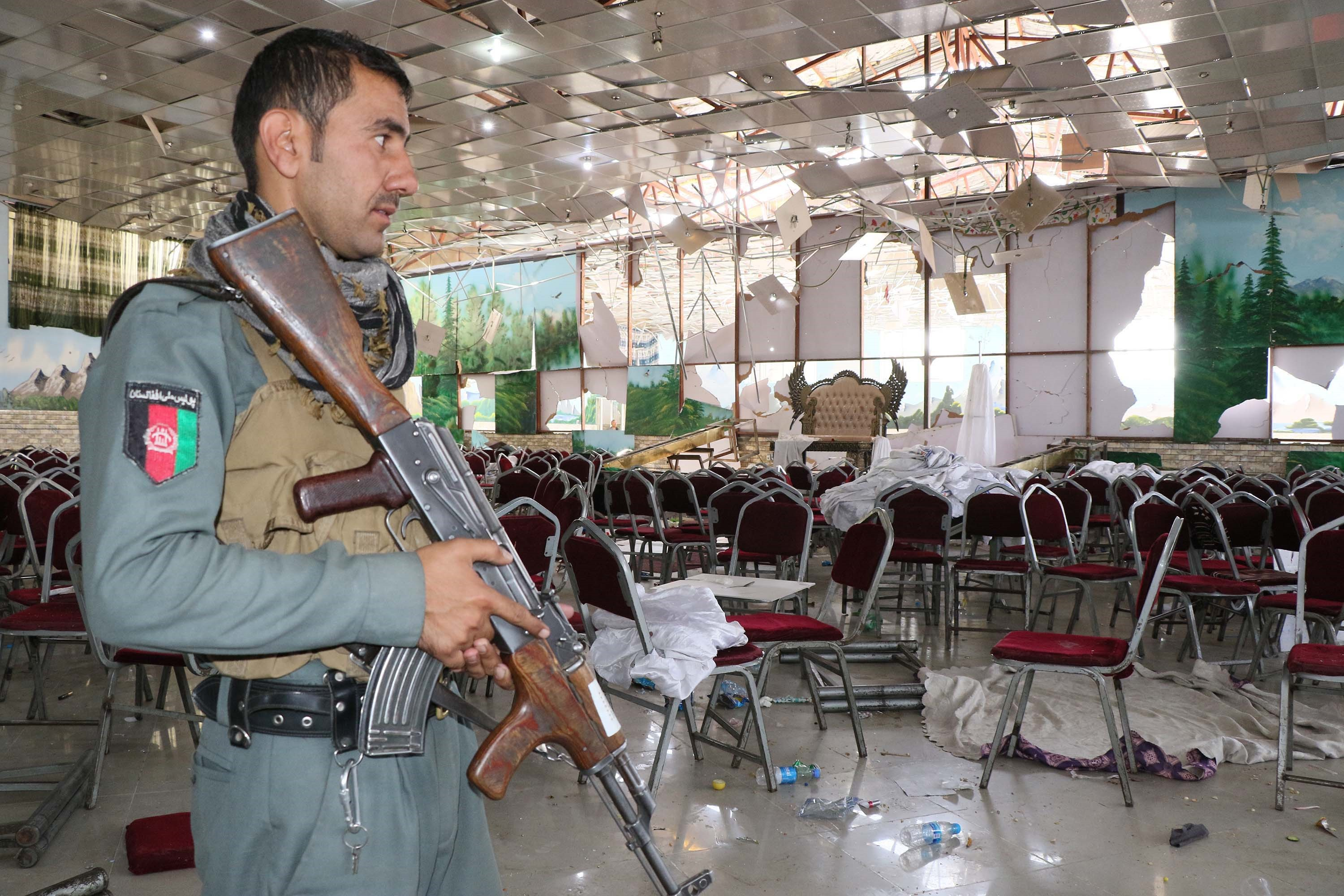 A uniformed security officer holds his rifle as he looks at a debris-filled hall with scattered chairs and a collapsing ceiling.