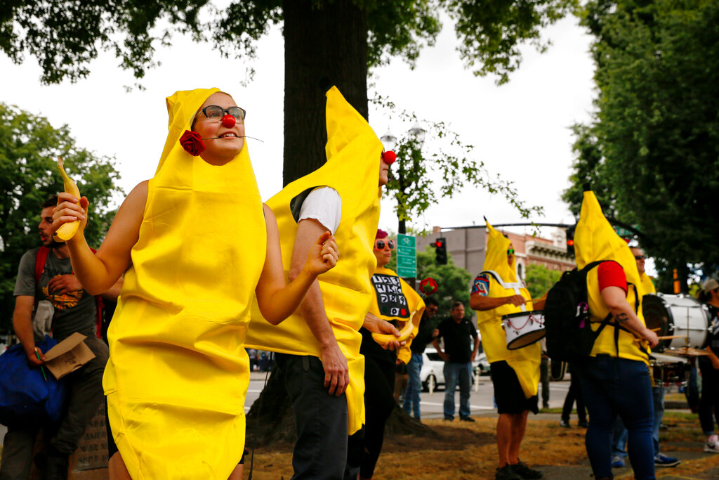 People in  banana costumes hold dance counter protest party in downtown Portland