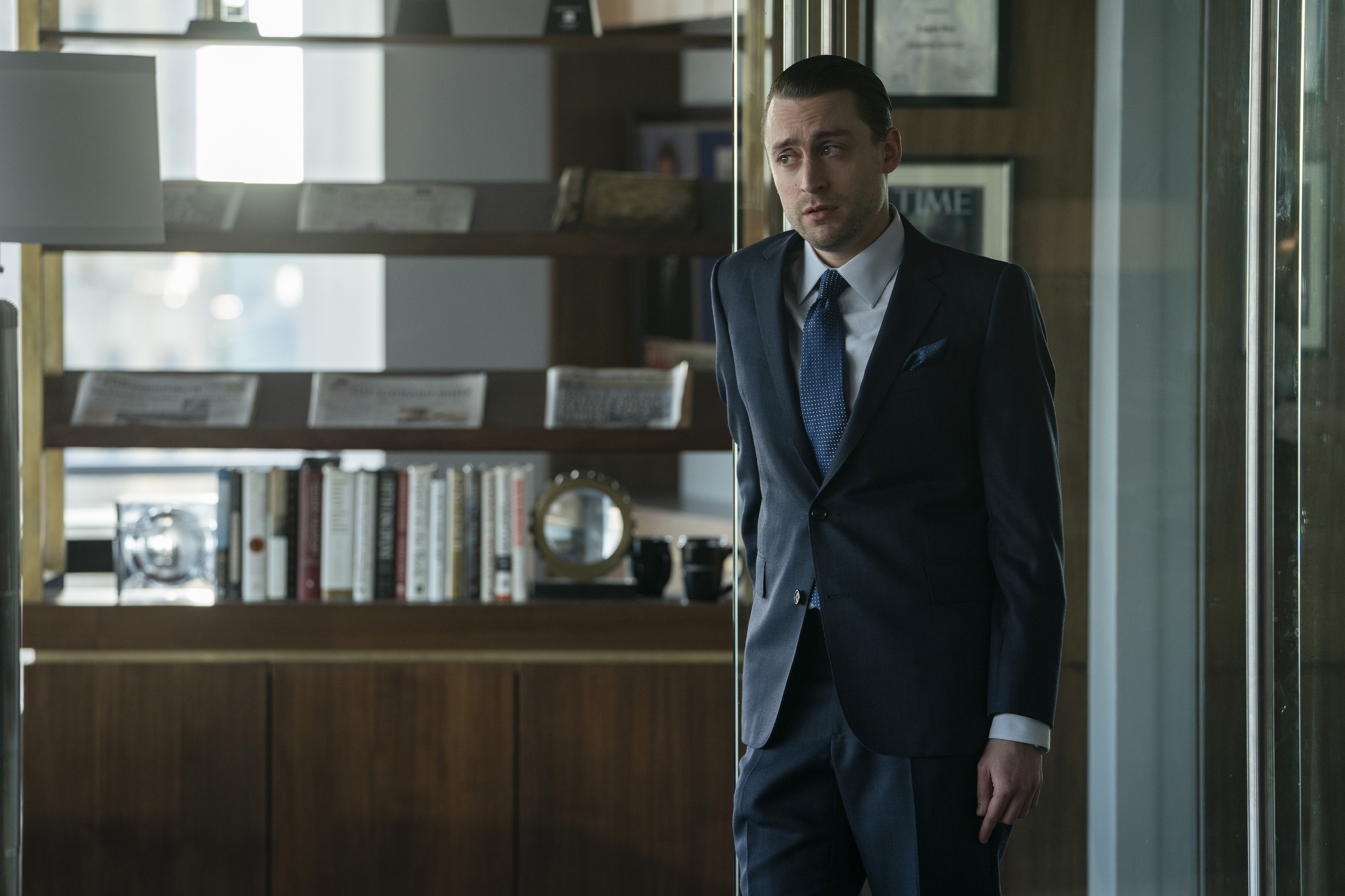 Roman (Culkin) raises an eyebrow as he stands in his father's office.