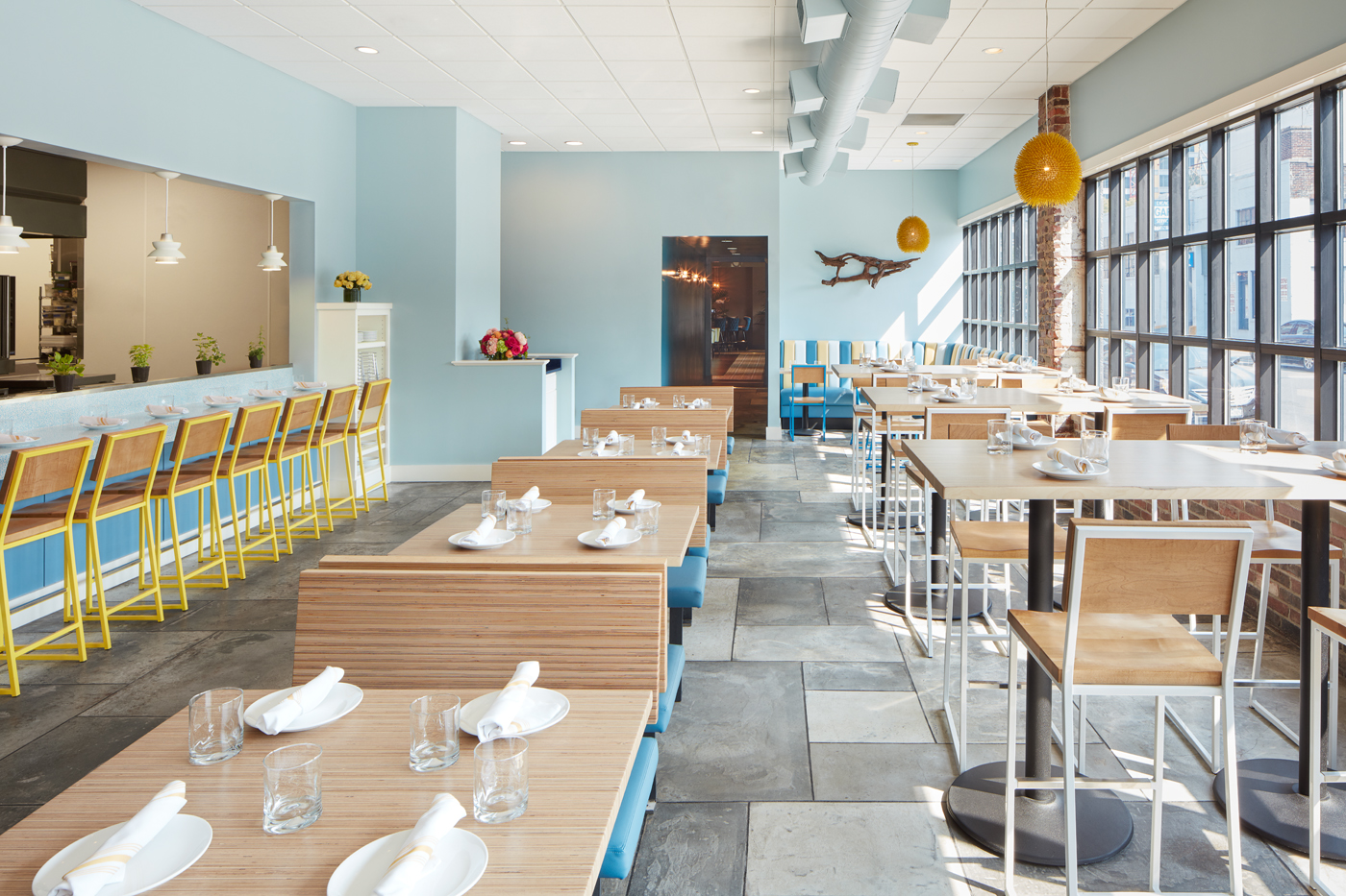 A bright restaurant space features light blue walls, wooden tables, and chairs with white metal bases