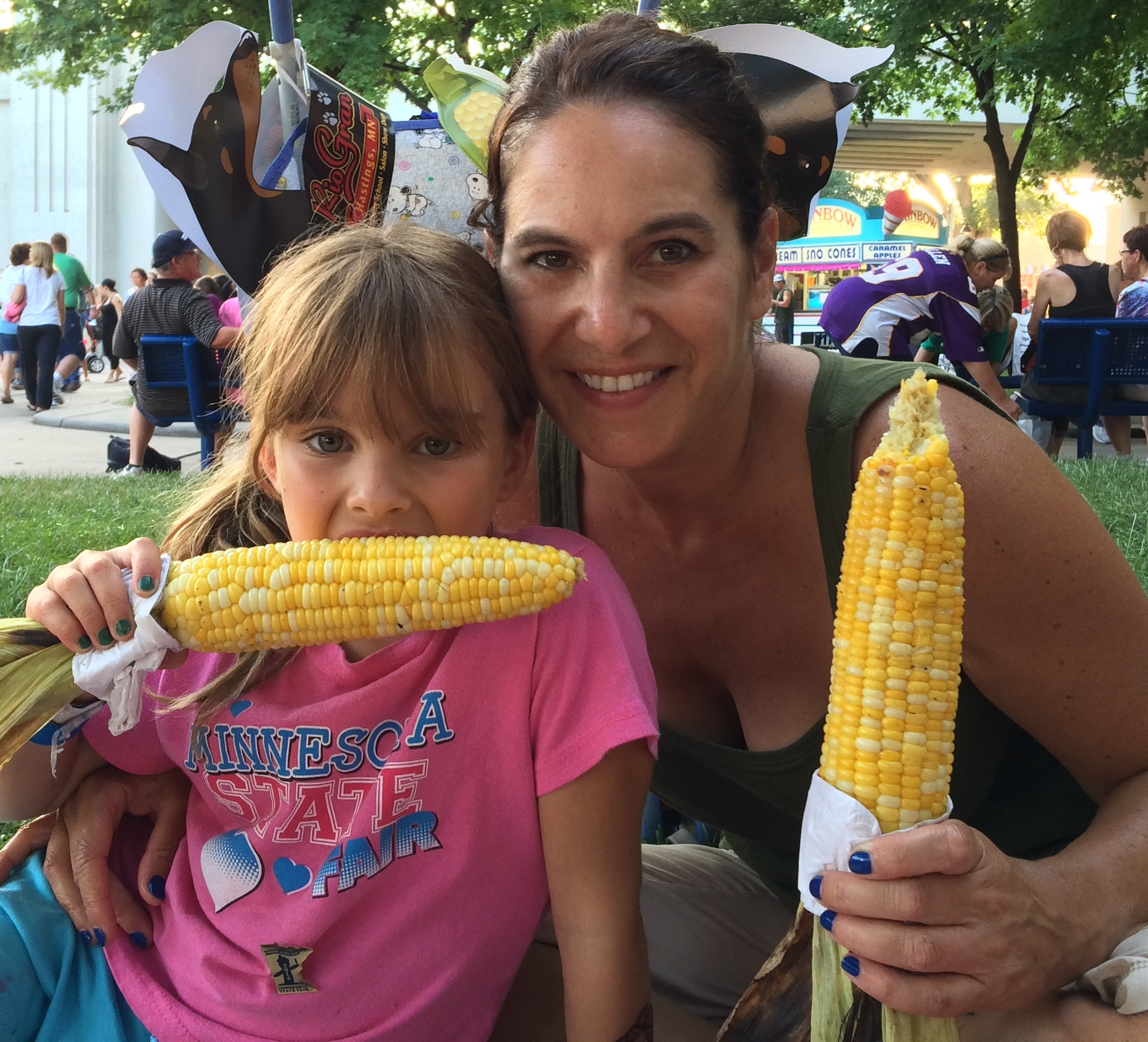 Writer Alex Lodner with her young daughter Millie, Millie's eating corn while Alex is holding a cob and smiling. Lots of people and bright fair vendor booths are behind them.