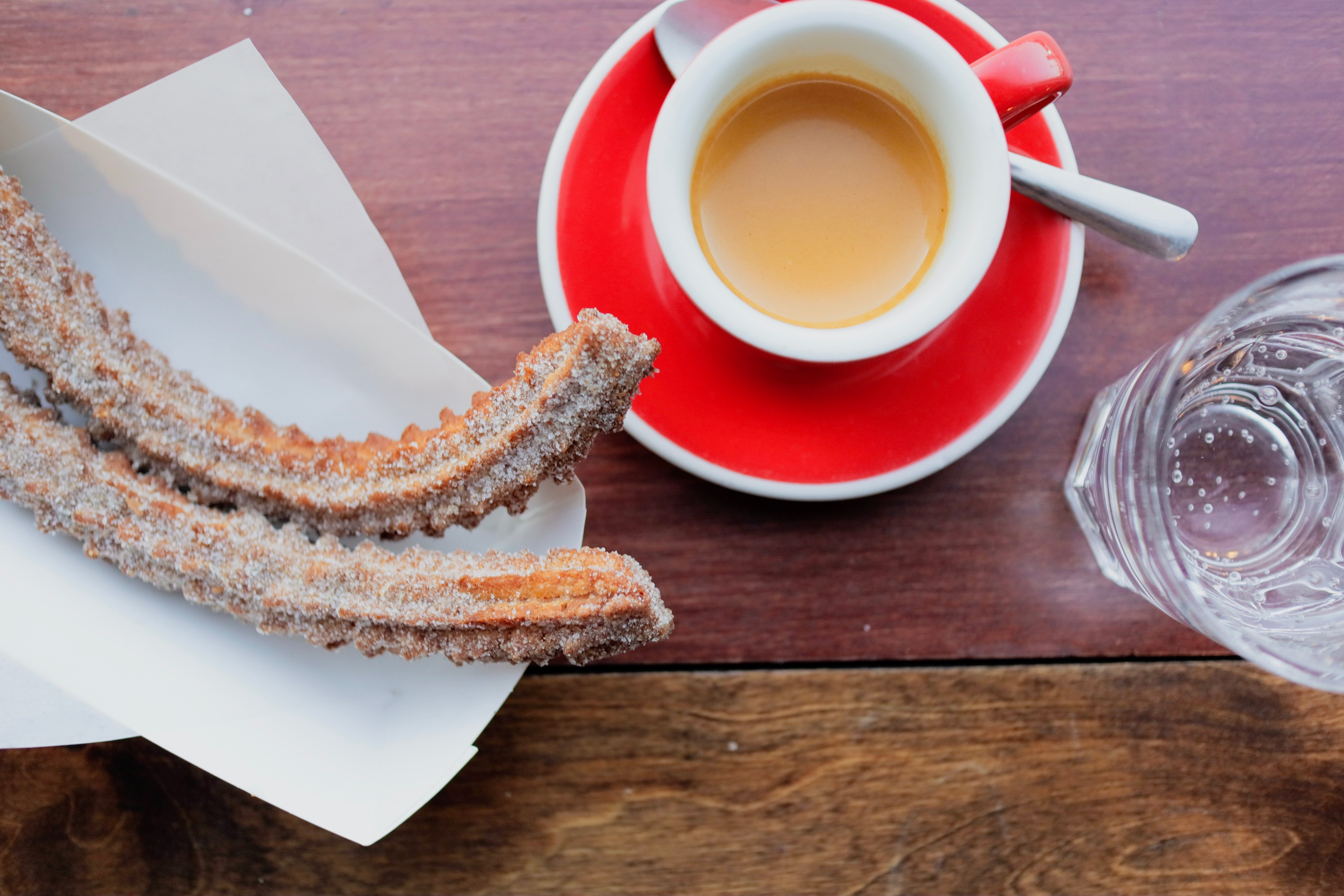 Two churros on a white tray next to a coffee in a mug on top of a red saucer next to a glass of water, all on a wooden table