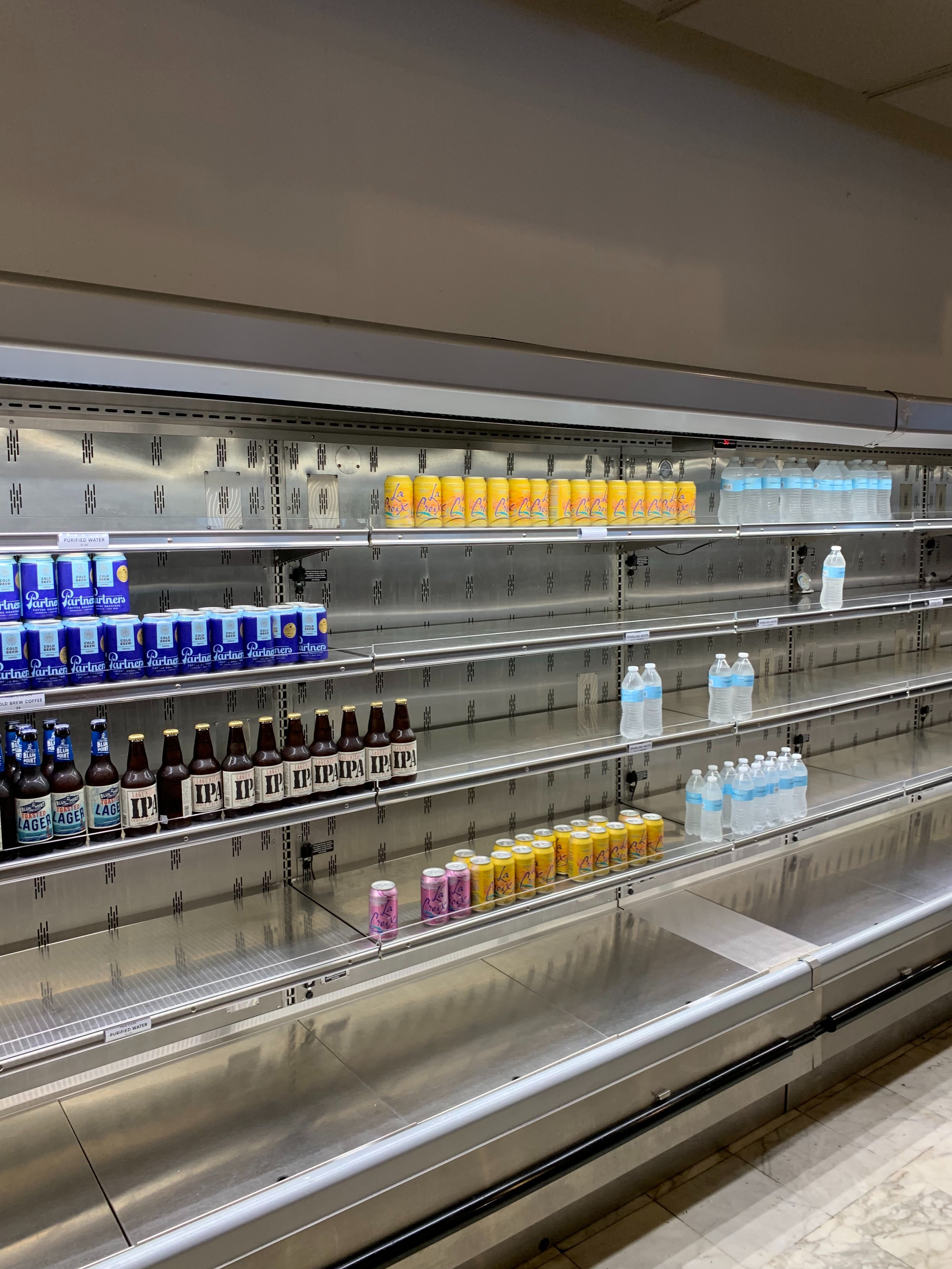 Store shelves that are mostly empty except for a few cold drinks