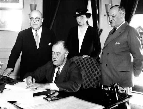 President Franklin D. Roosevelt signs the Wagner Unemployment Bill during the Great Depression with Rep. Theodore A. Peyser, D-N.Y.; Labor Secretary Frances Perkins and Sen. Robert Wagner, D-N.Y.