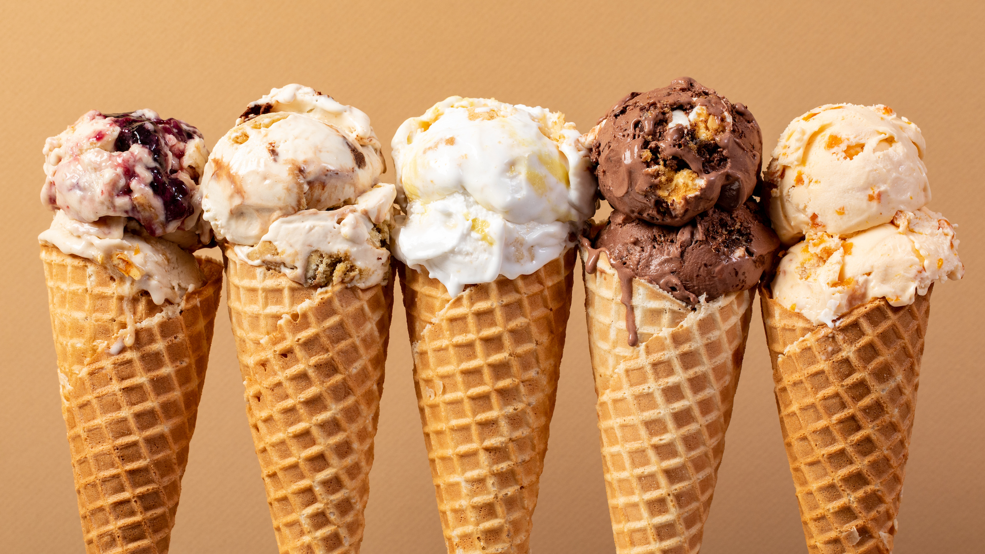 Ice cream of varying flavors drip down on waffle cones.