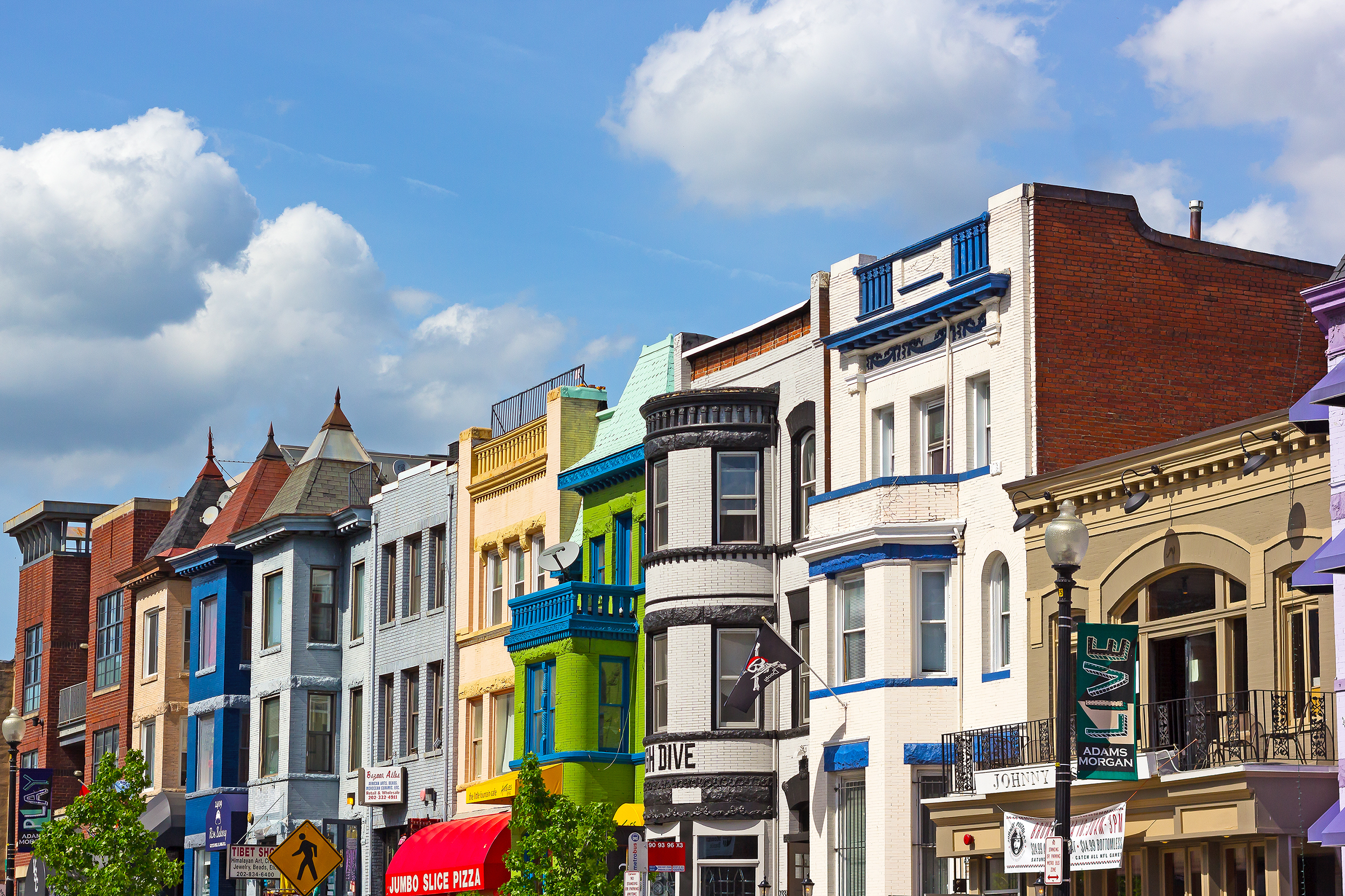 A row of buildings housing businesses on 18th Street NW in Adams Morgan. The buildings are of various colors but most are three stories.